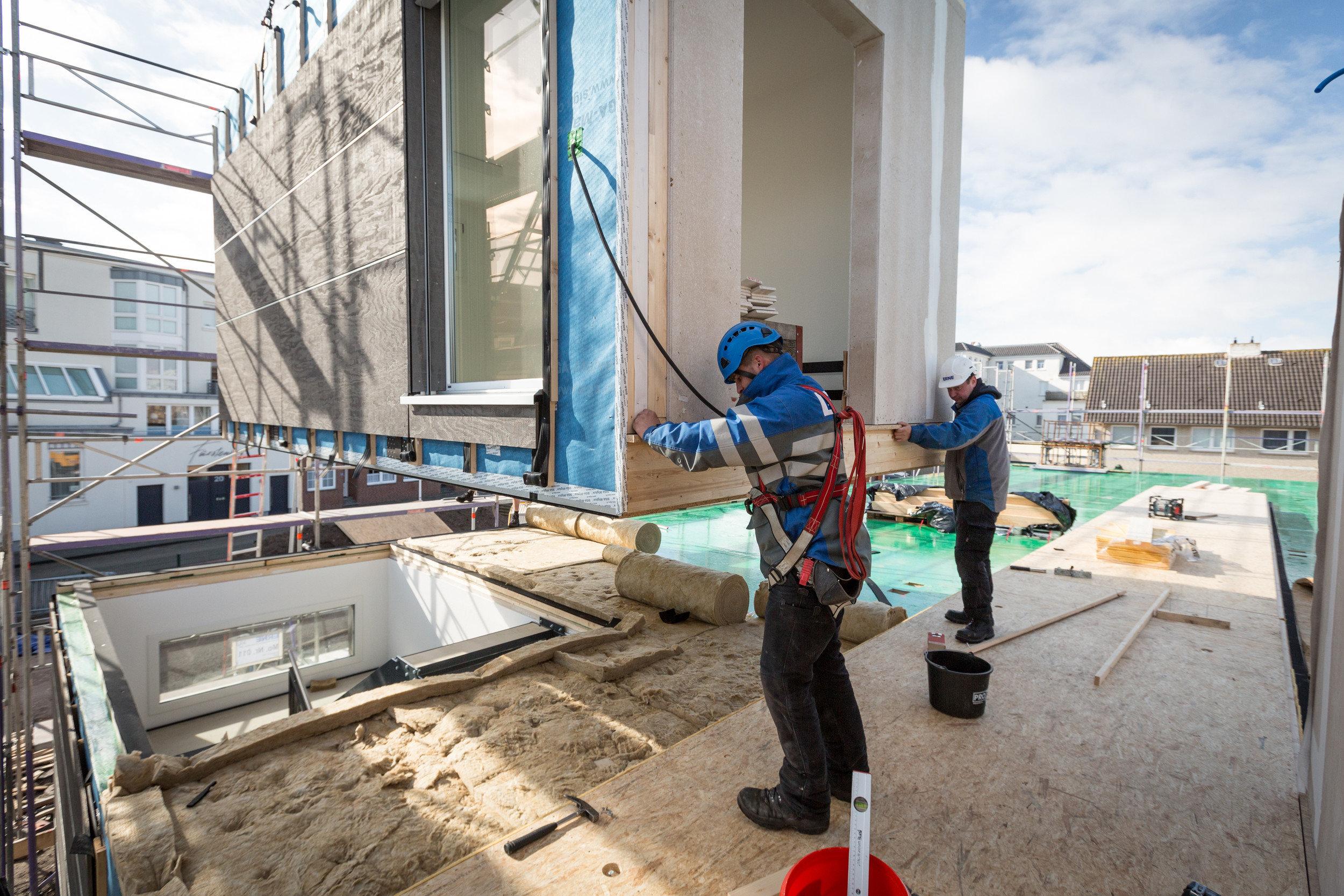 Bauarbeiter platzieren ein Modul auf Baustelle
