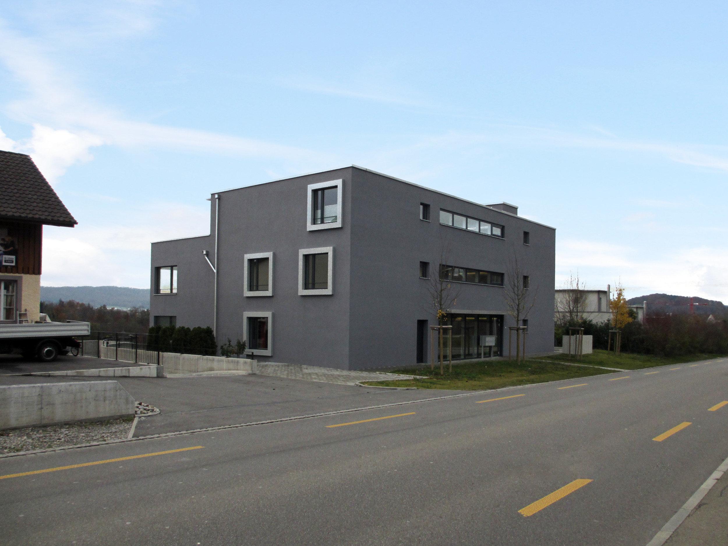 3-geschossiges MFH mit 4 quadratischen Fenstern auf linker Seite