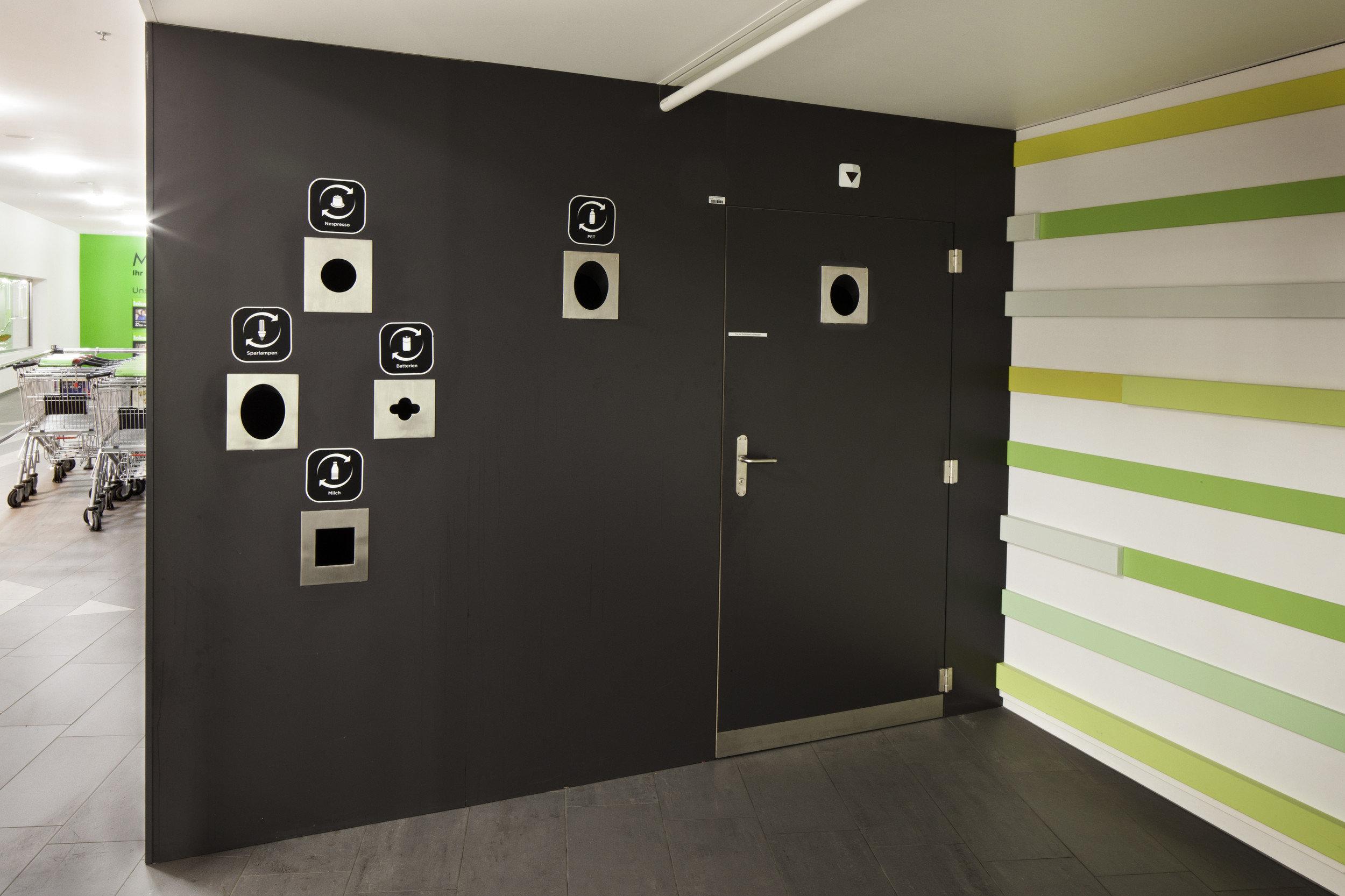 Schwarze Wand mit versteckt wirkender integrierter Brandschutztür