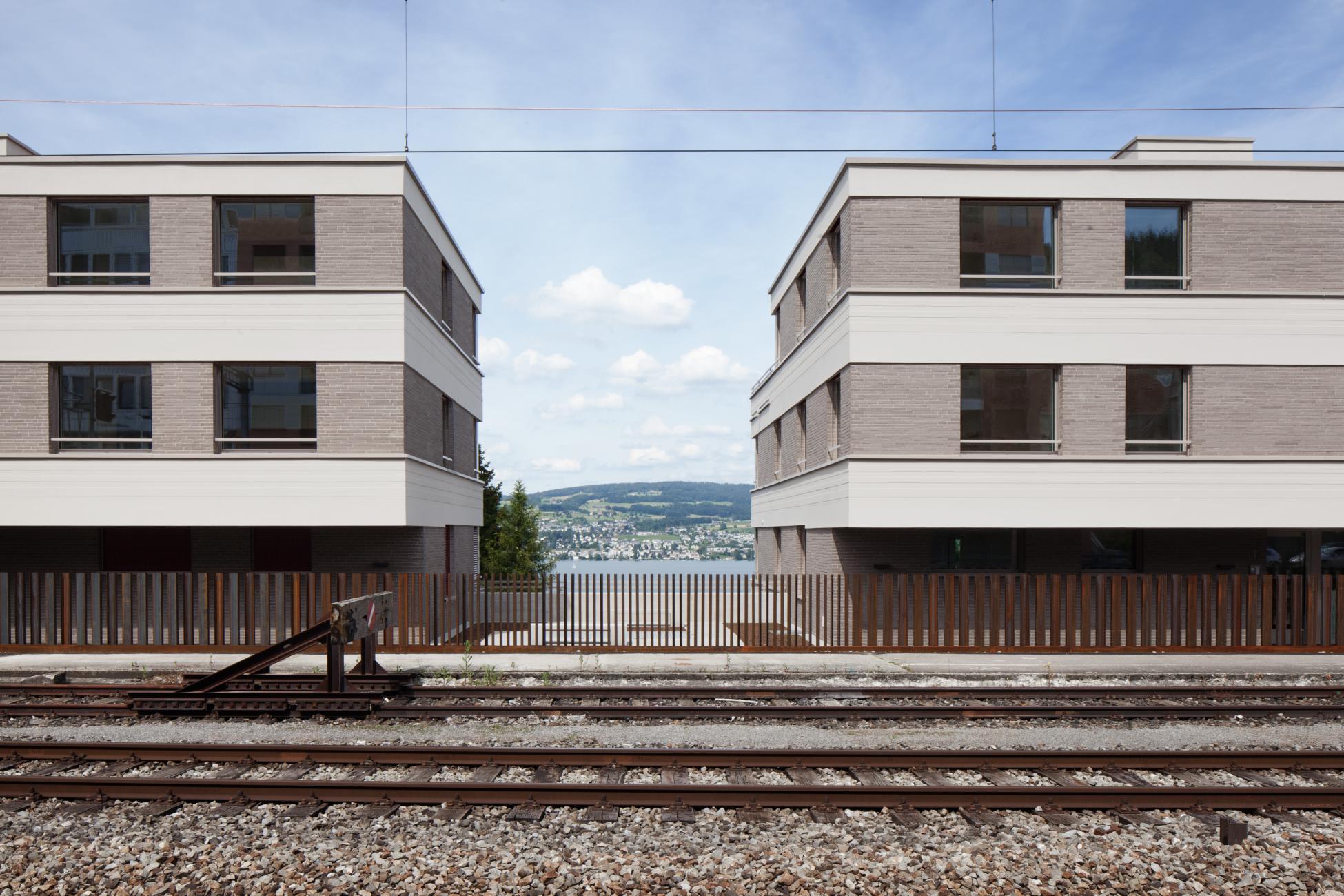 2 gleiche 2-stöckige Wohnblöcke mit gleichmässiger Fensteranordnung am Bahngleis