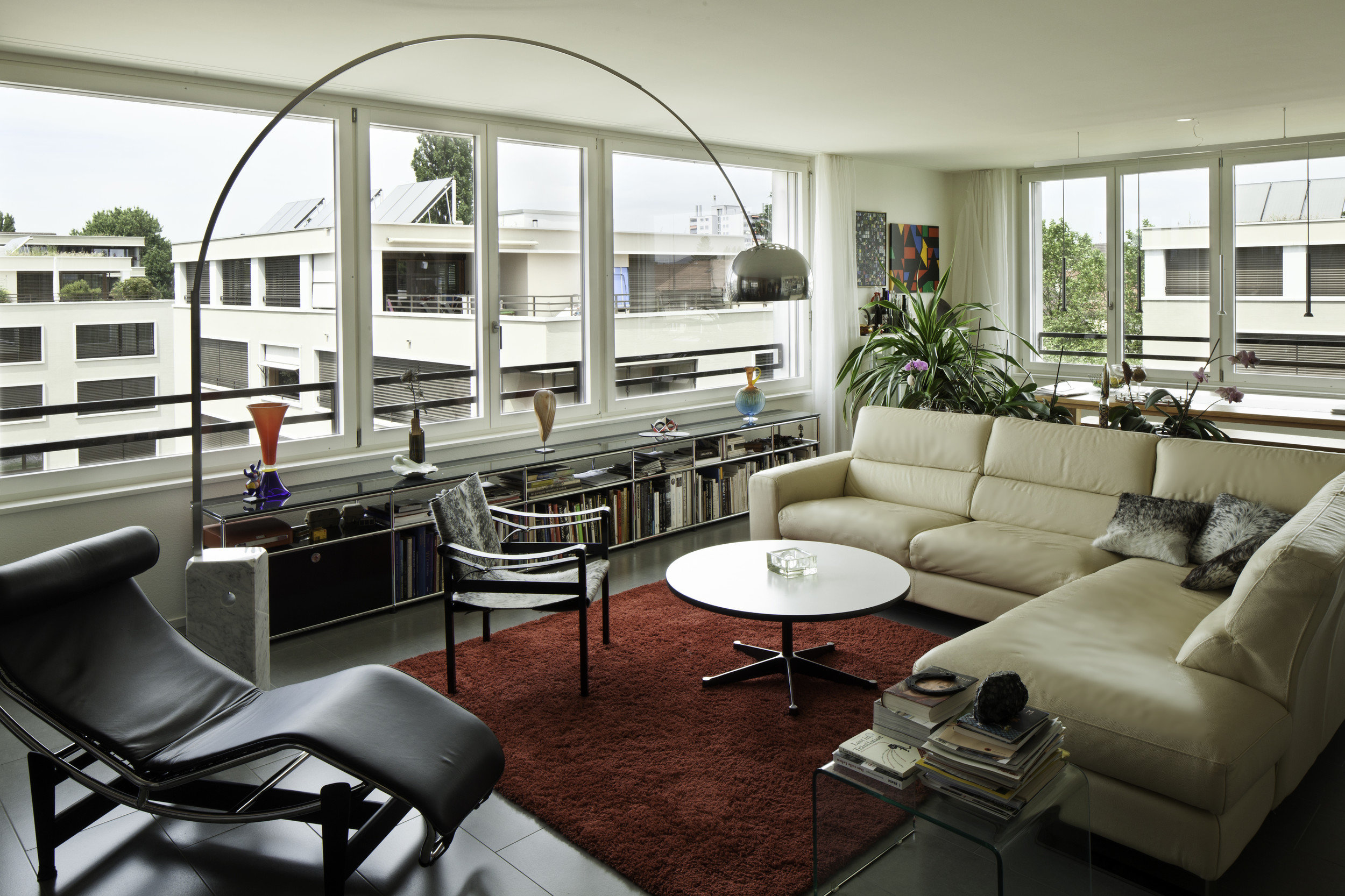 Wohnzimmer modern möbiliert mit grossen wandersetzenden Holz(-Metall)fenstern
