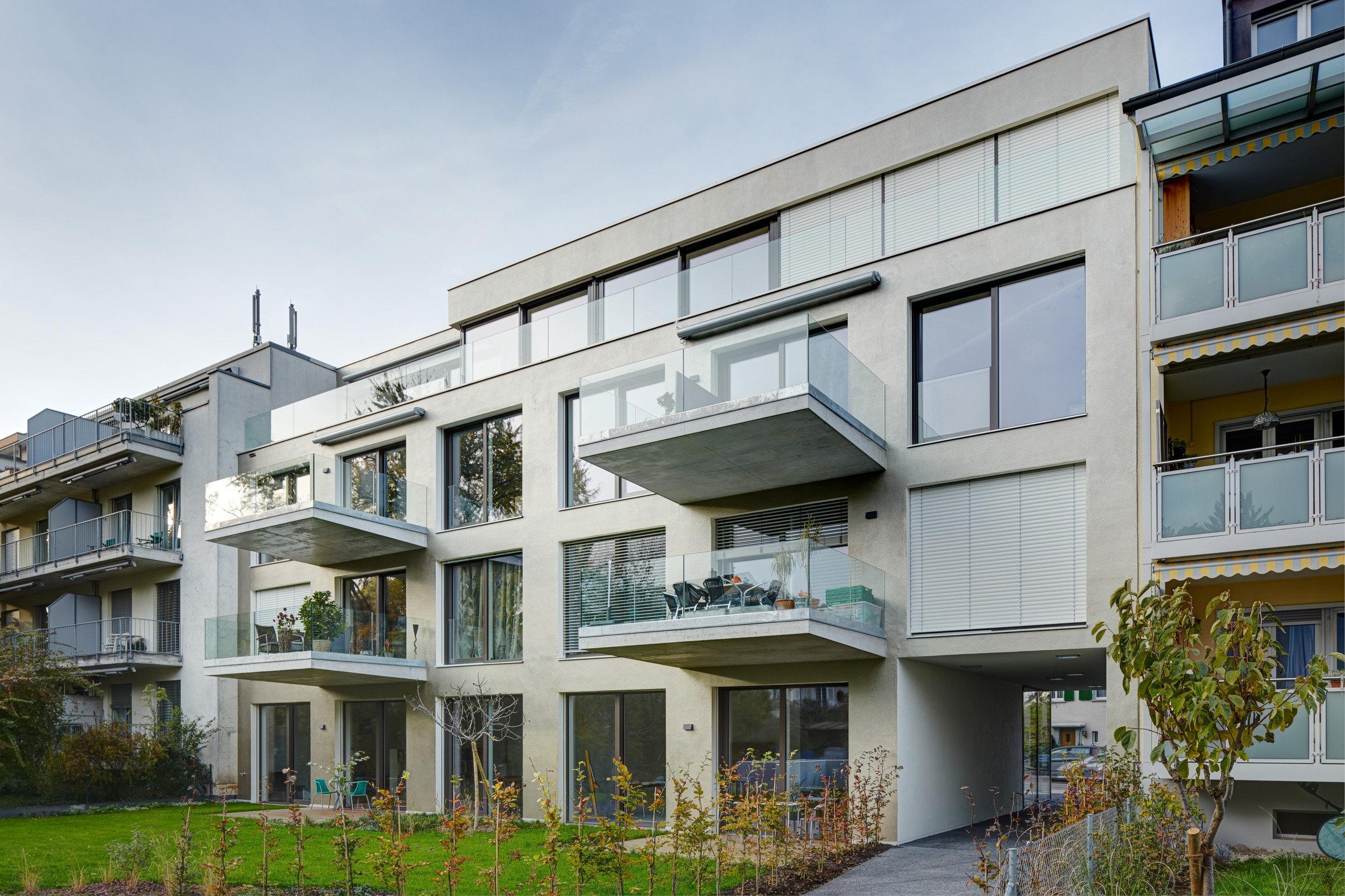 Mehrstöckiges Wohnhaus aus Beton mit gleichmässiger Anordnung von raumhohen Fenstern
