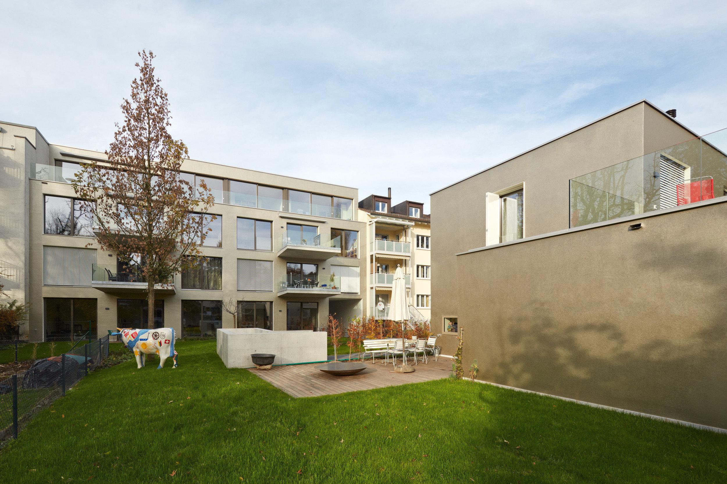 4-stöckiger Beton-Wohnblock hinter 2-stöckigem Beton-Wohnblock mit Grünfläche