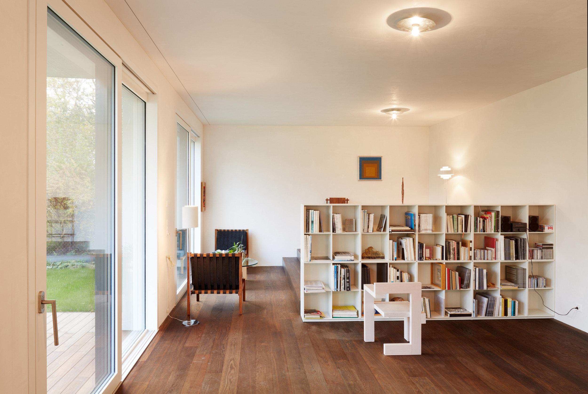 Möblierter Raum mit Bücherregal und Hebe-Schiebetüren in hellem und modernem Design