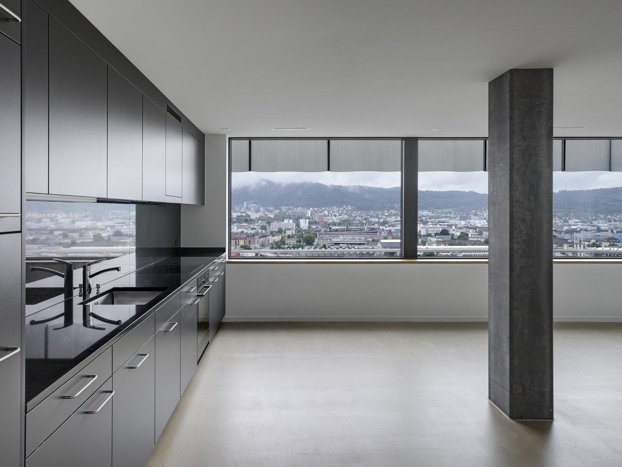 Gunkle moderne Einbauküche links mit grossen lichtspendenden Fensterelementen, links schwarze Säule