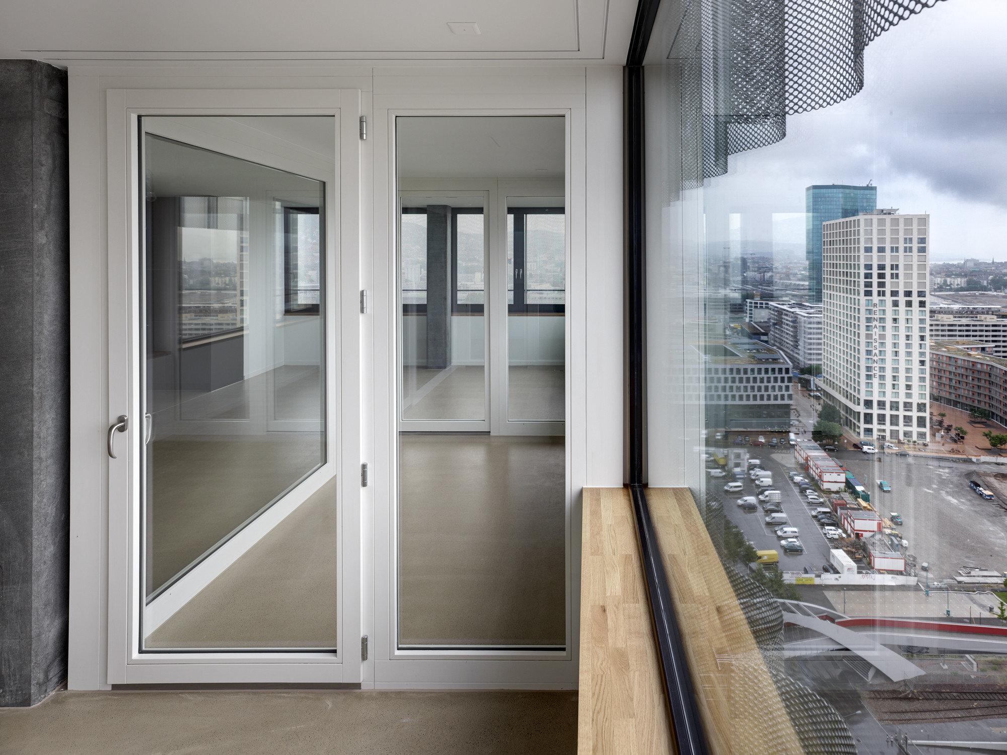 Grosse moderne Holztüre ausgefüllt mit Glas die Räume neben grossen Fenster mit Licht durchfluten