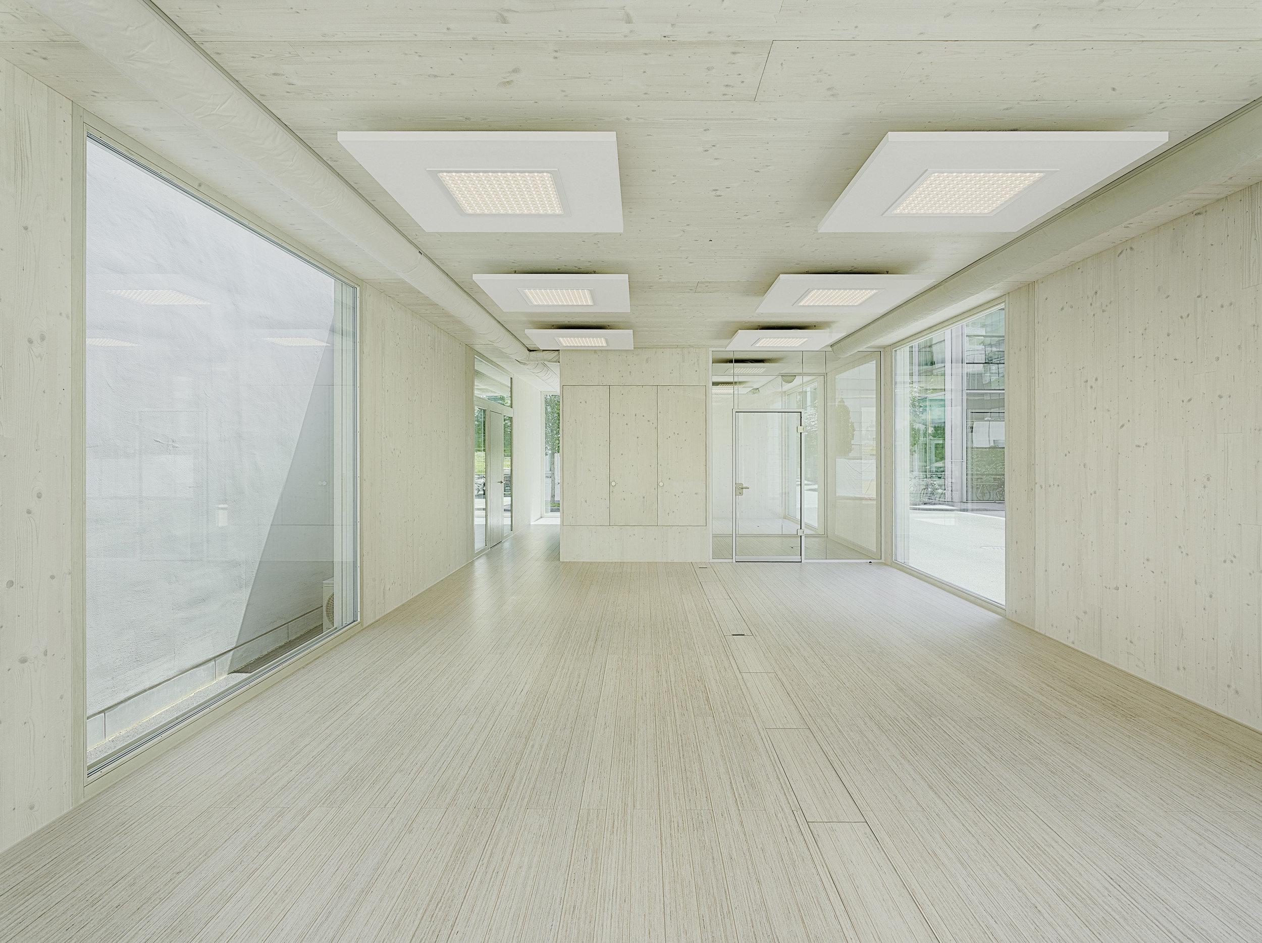 Leerer Raum aus sichtbarem Massivholz und beidseitig festverglasten raumhohen Fenster