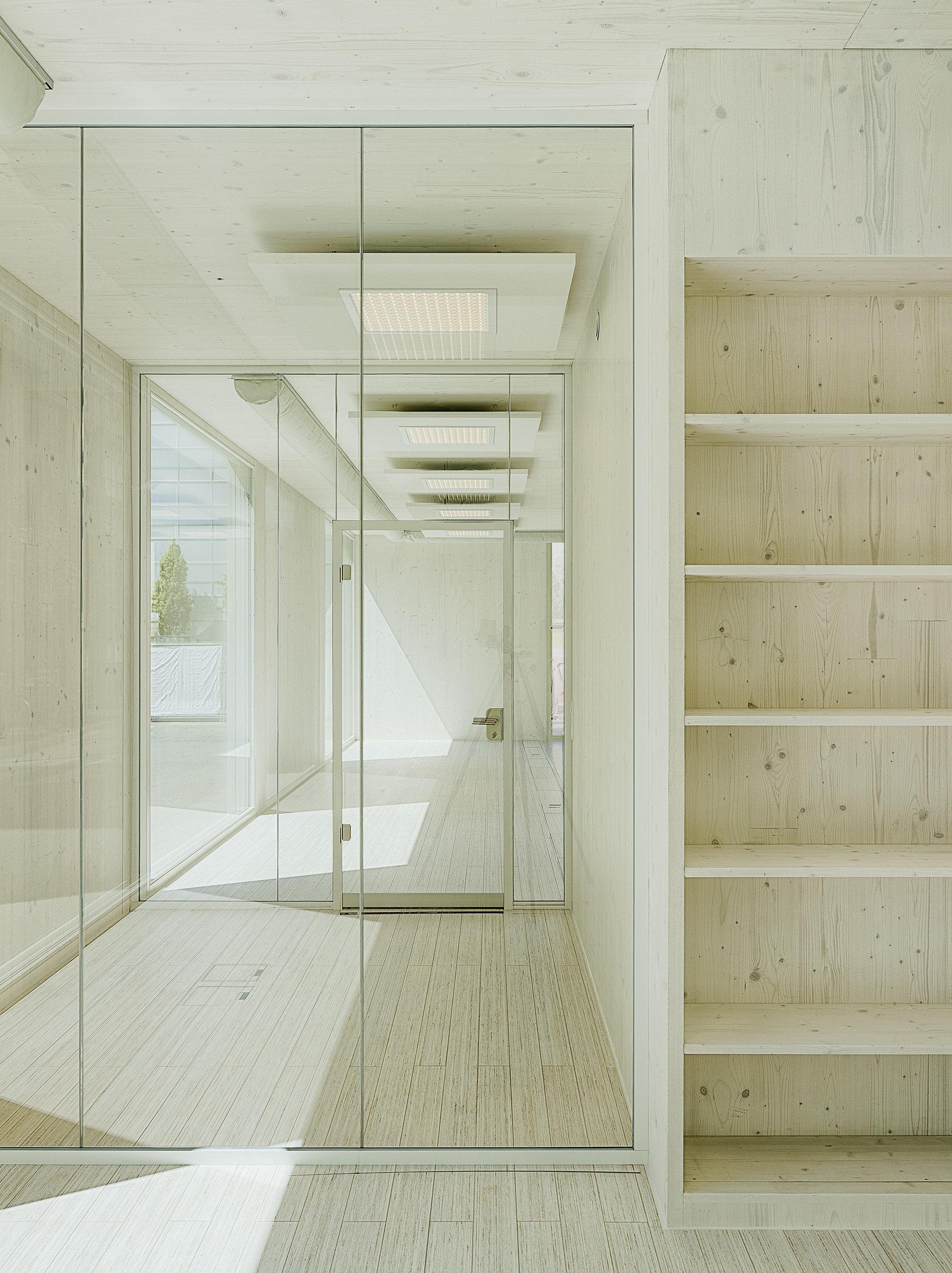 Regal aus Massivholz neben Festverglasung mit dahinterliegender 3m hohen Glastür
