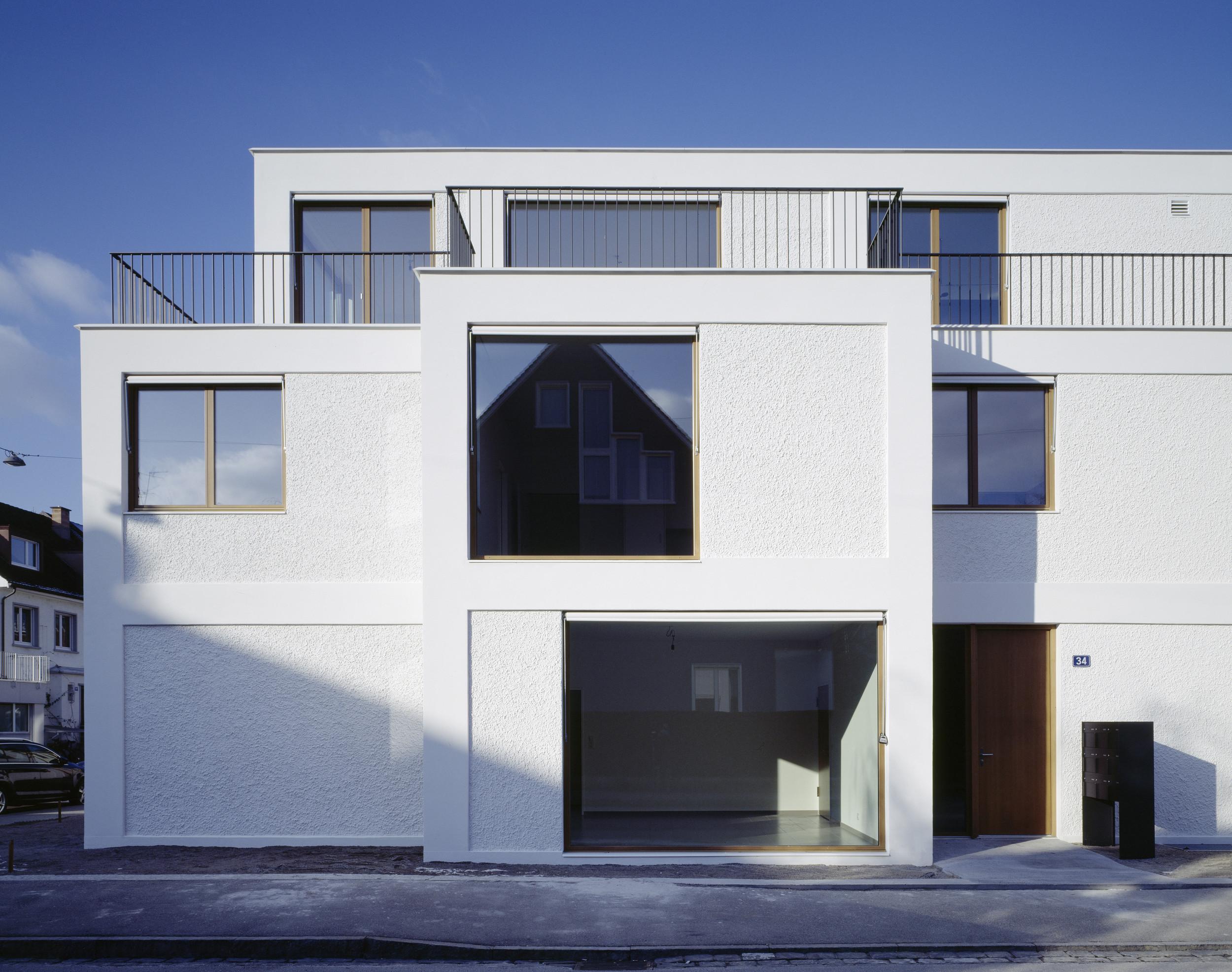 3-geschossiges Wohngebäude mit verschieden grossen Fenstern und weisser Fassade