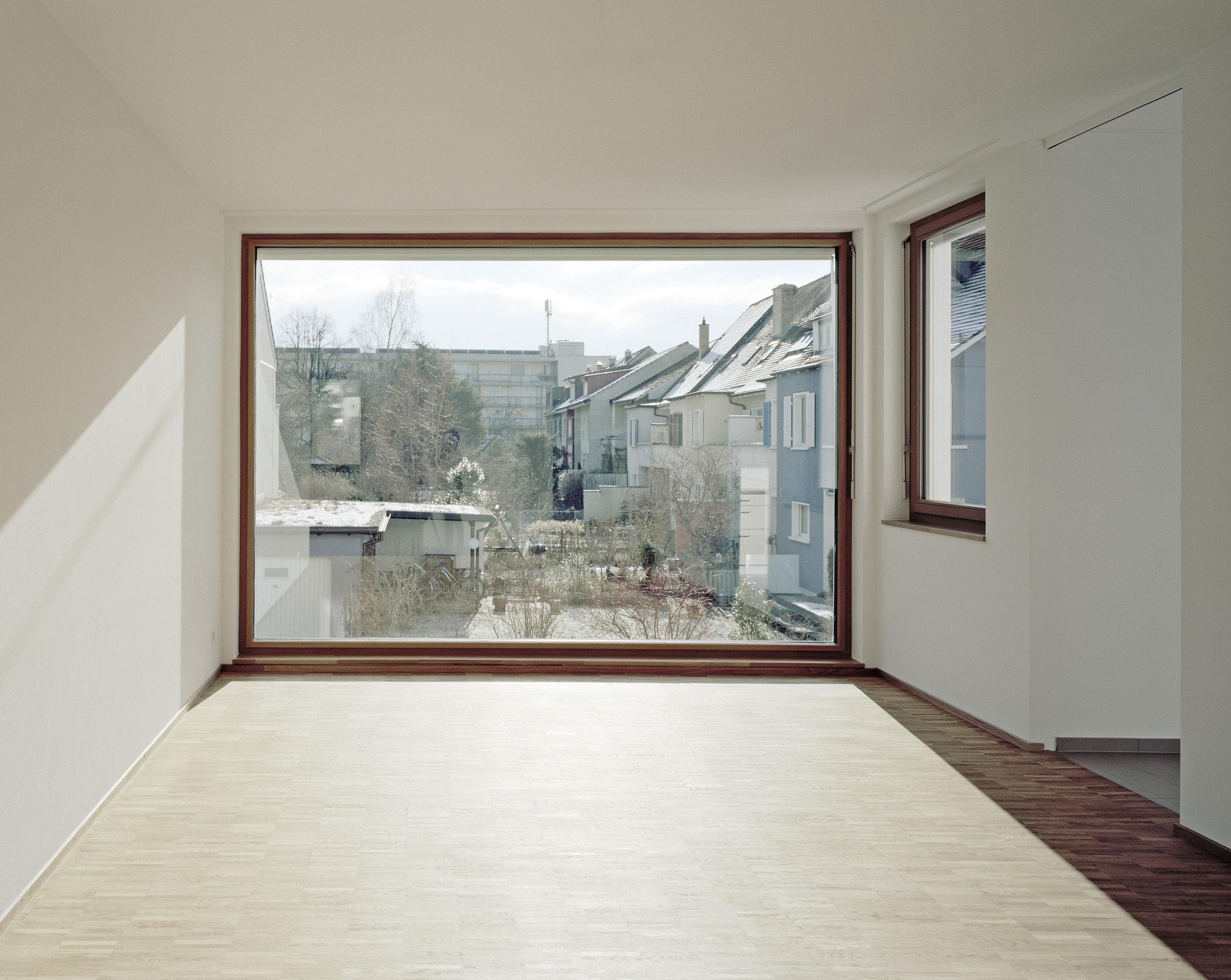 Holzfenster welches die ganze Wand ausfüllt und den Raum mit Licht durchströmt