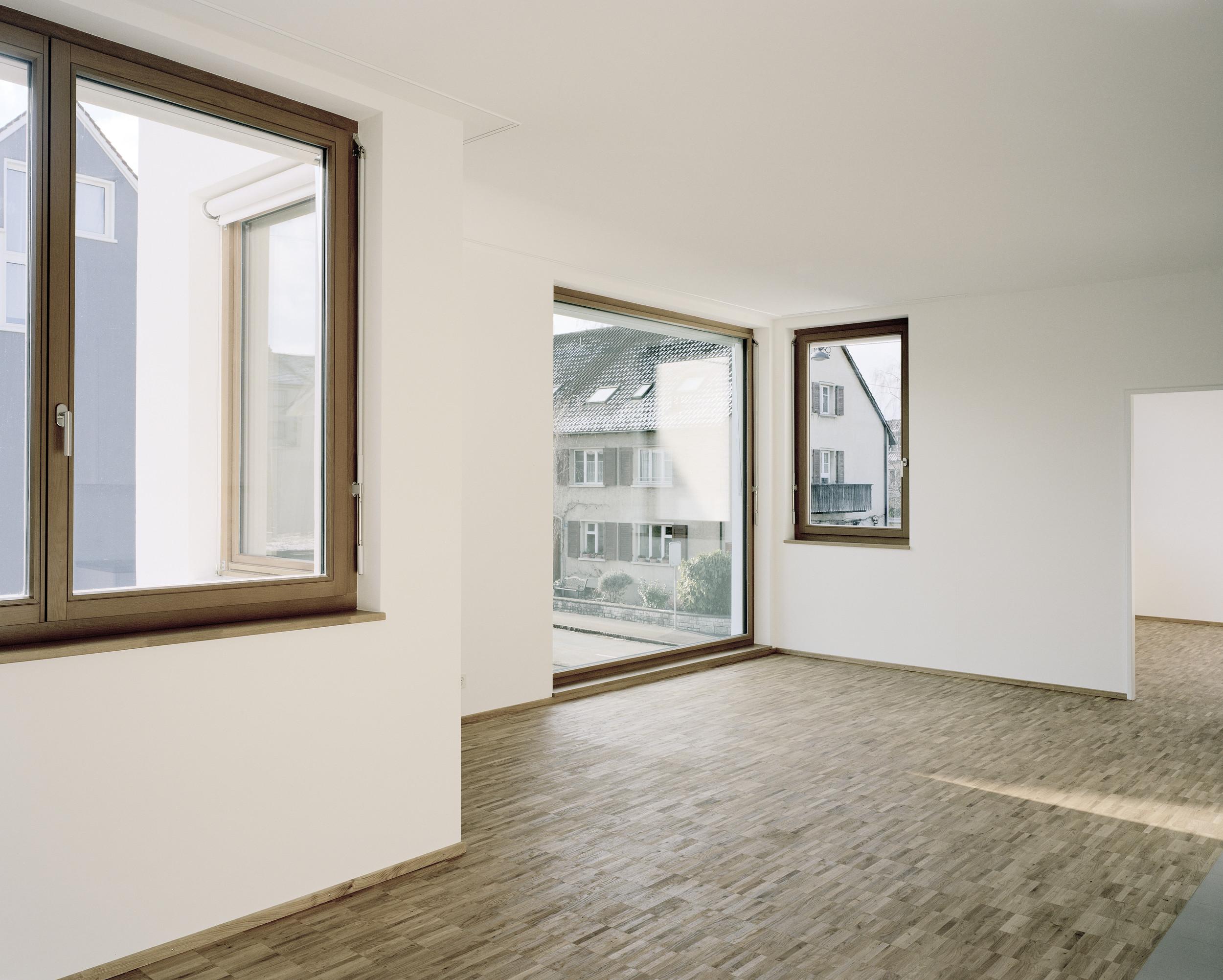 schräge Ansicht auf verschieden grosse lichtspendende Kieferholzfenster von innen