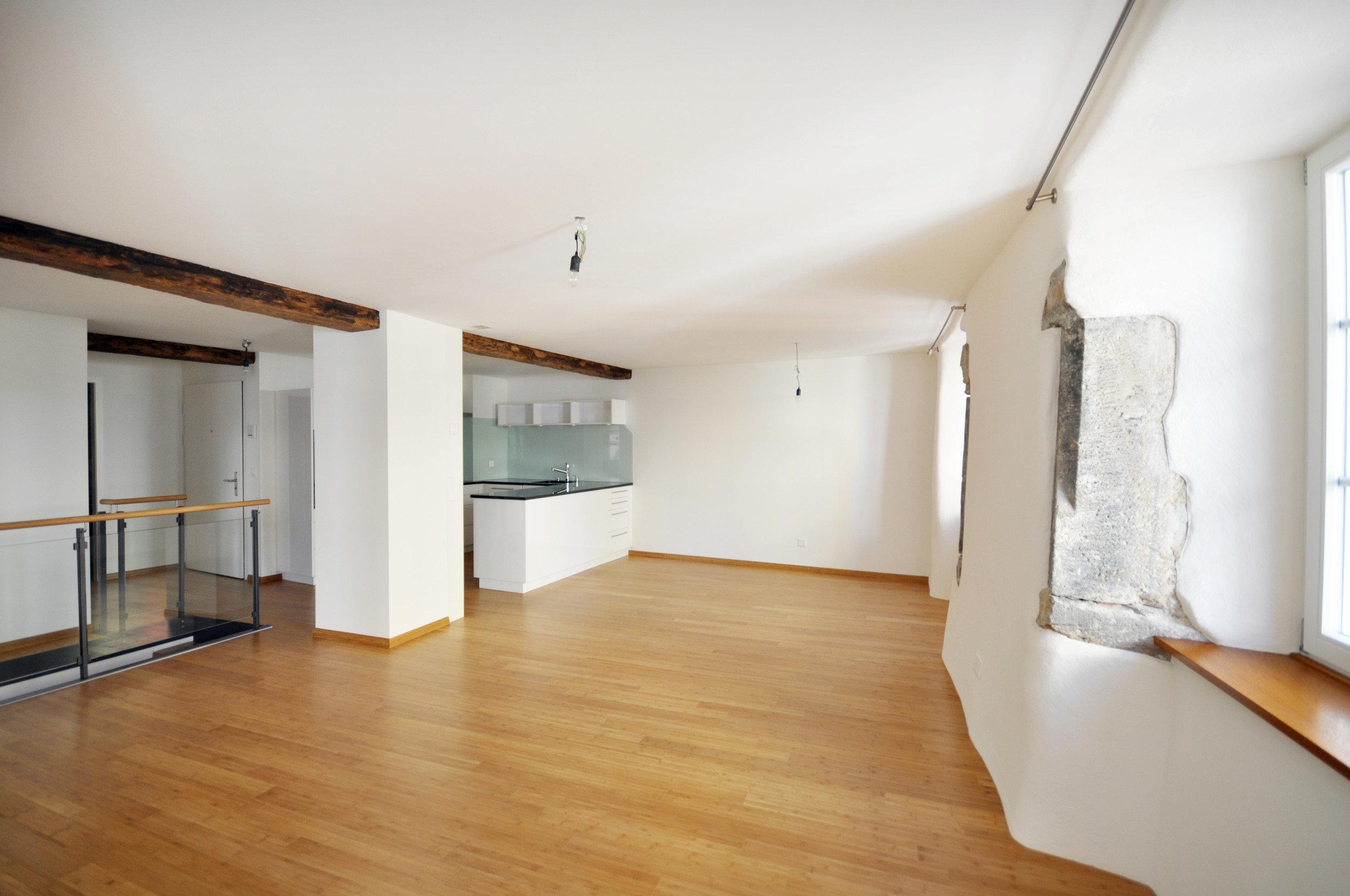 grosser lichtdurchfluteter renovierter Raum mit alten Steinplattenteilen in der Wand