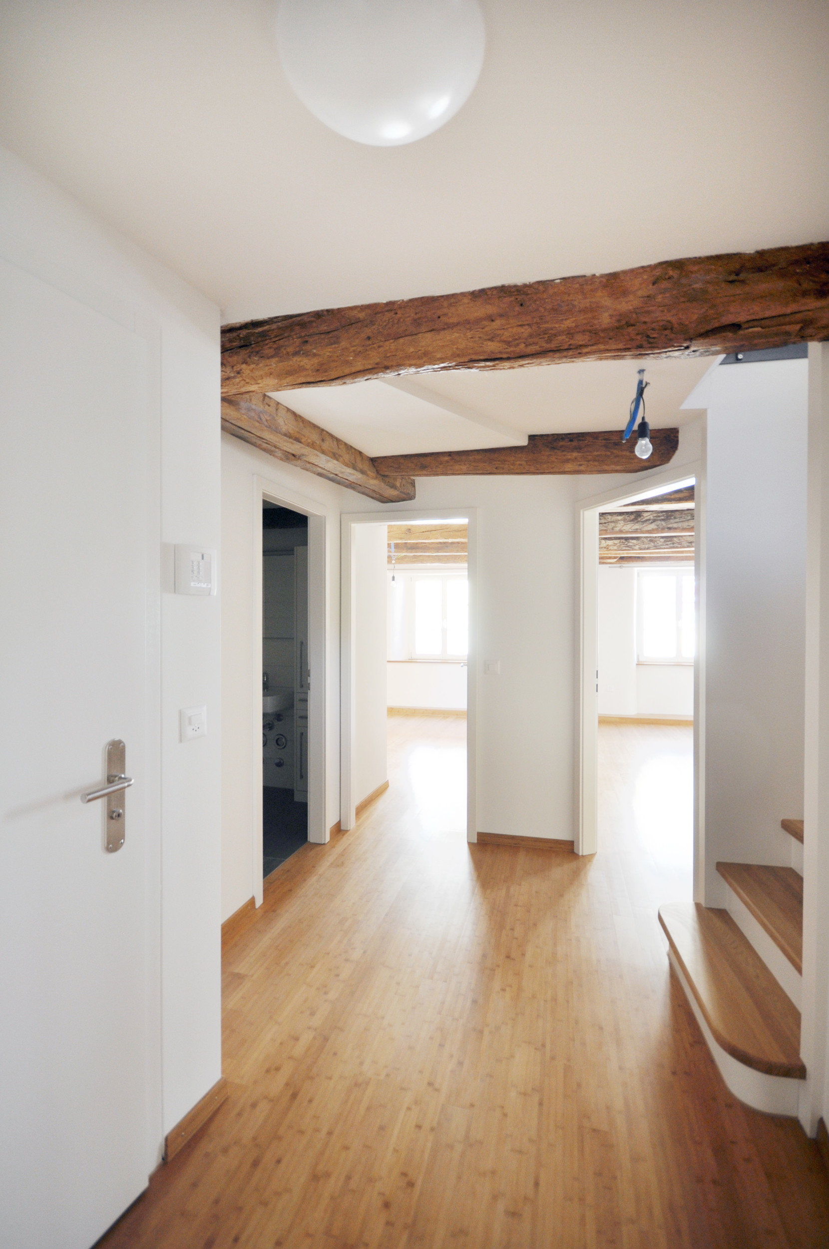 Renovierter Flur mit Holzdielenboden und Sicht auf zwei lichtspendende Fenster