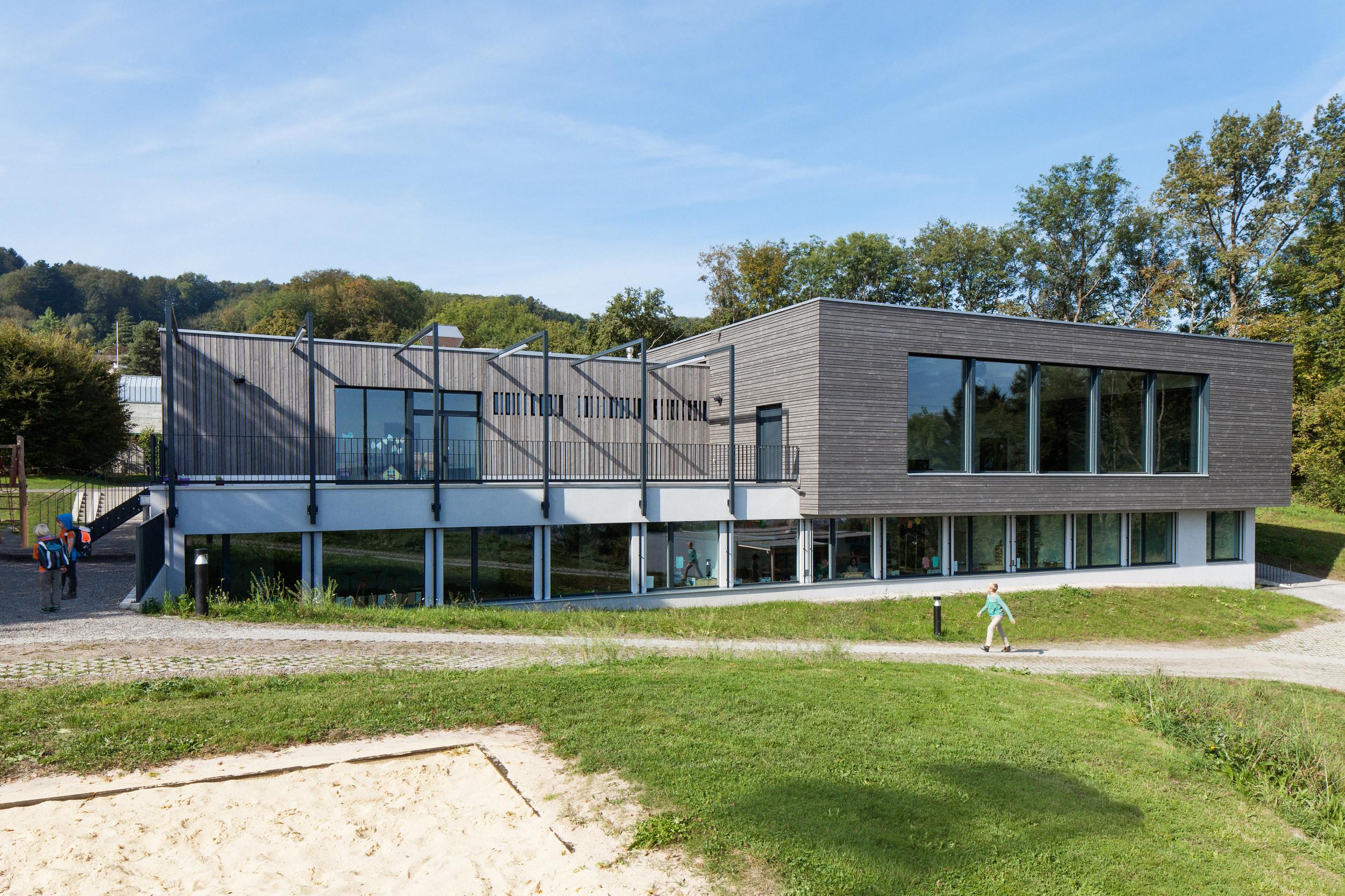 Saniertes Schulhaus mit Holzfassade bei 2. Geschoss