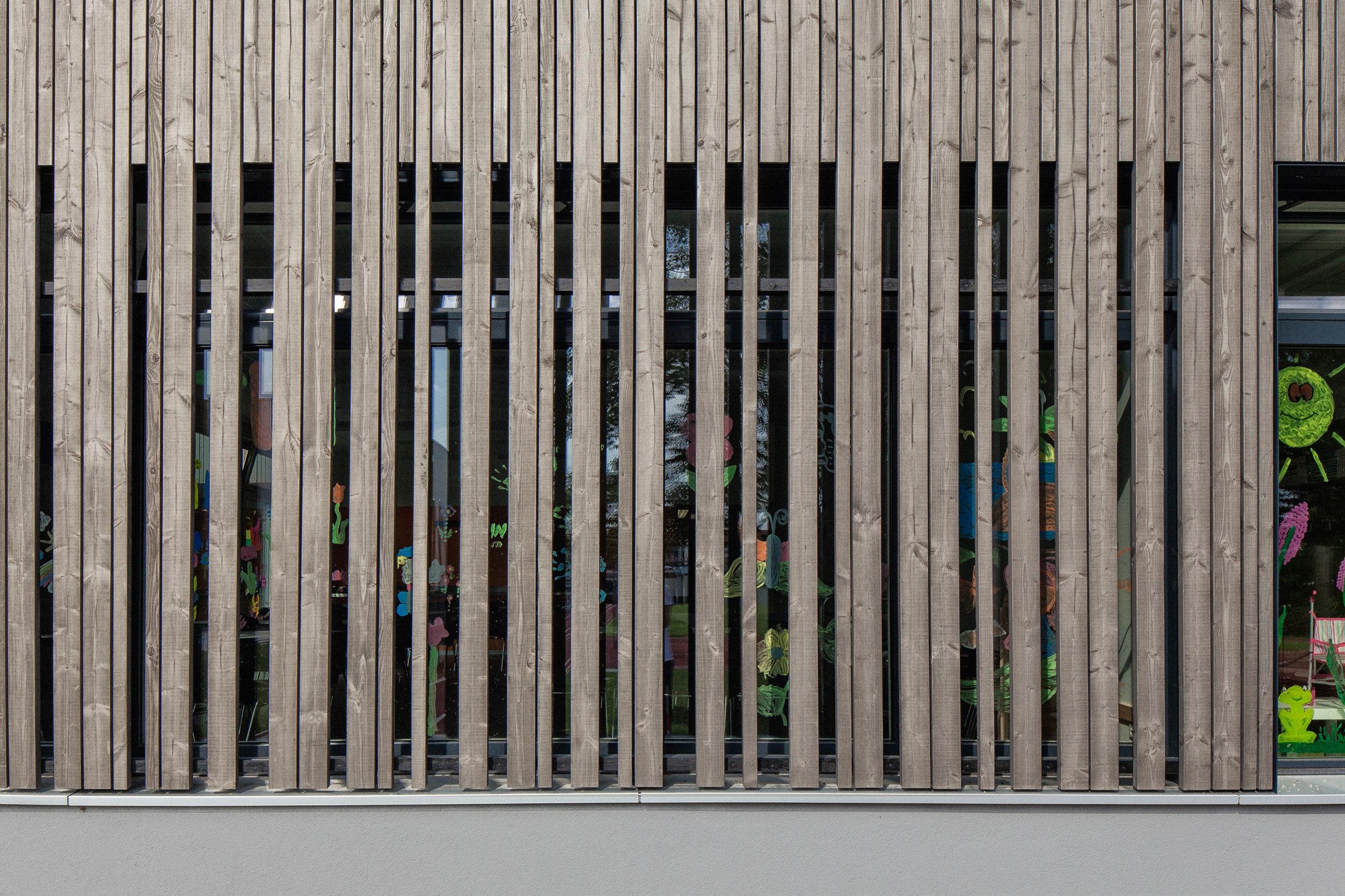 Fokus auf moderner Holzfassade vor Fenster bei Schulgebäude