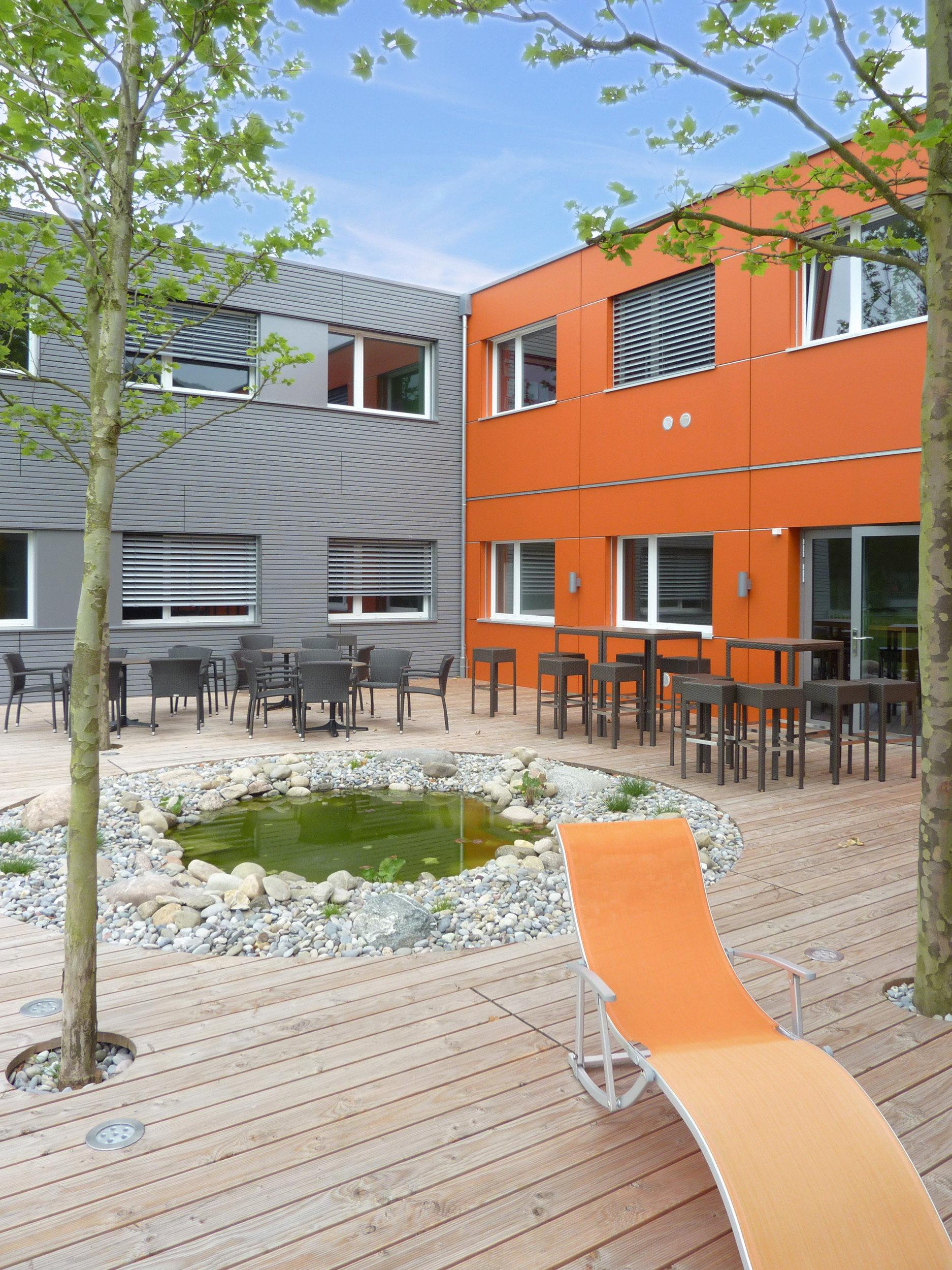 Veranda Bürogebäude mit Teich und Garnituren
