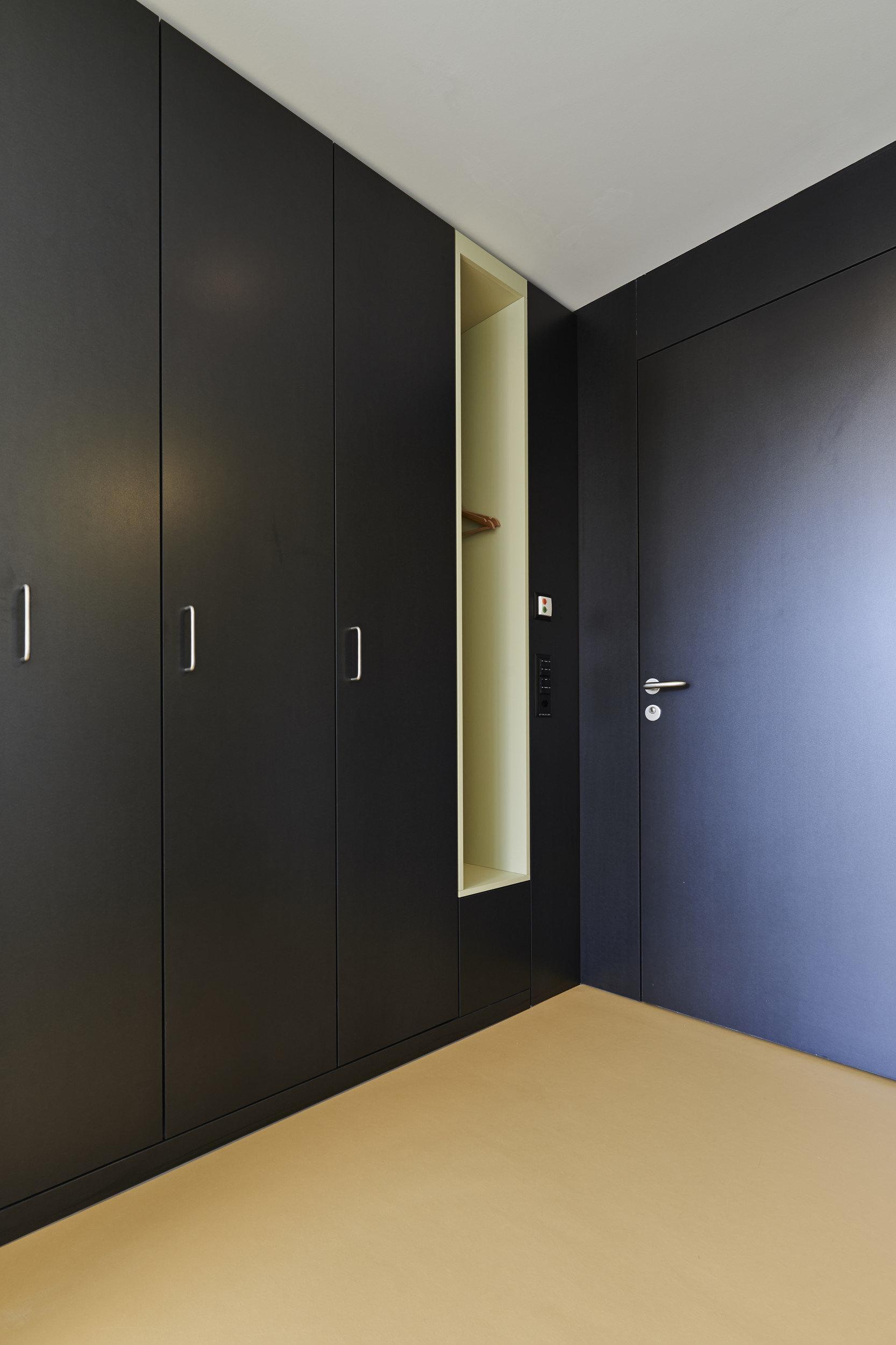 Wand mit schwarzen Holzschränken und schwarzer Holztür