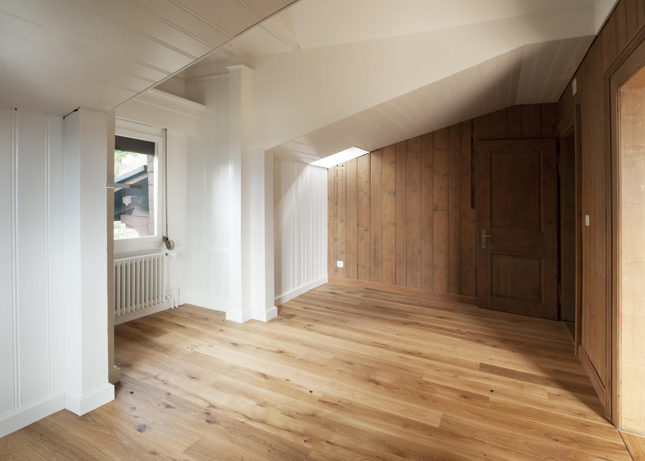 Wohnraum mit Wänden und Dachschräge aus Holzdielen in weiss
