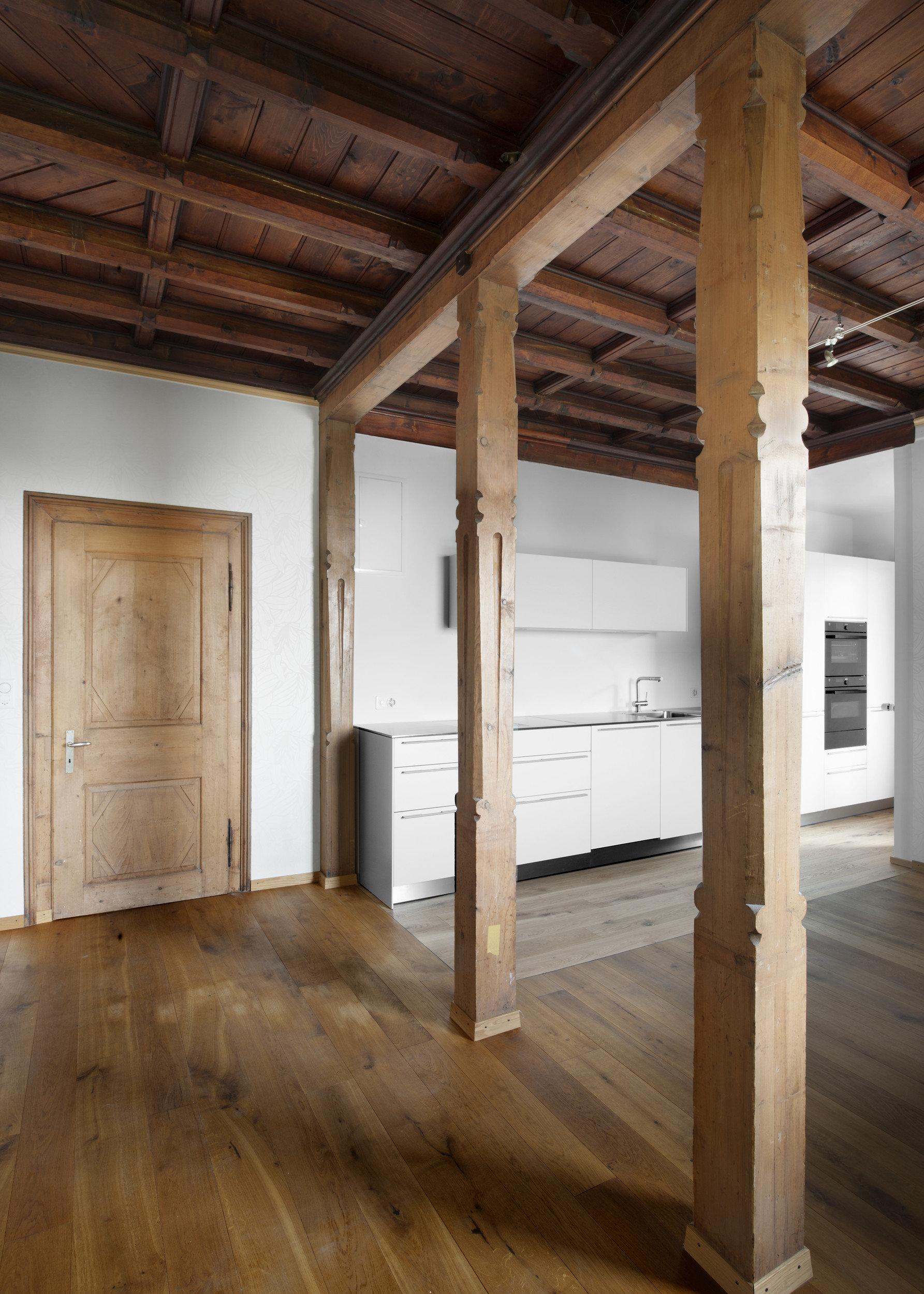 Wohnraum mit Holzbalken welche die Decke stützen + moderne Einbauküche