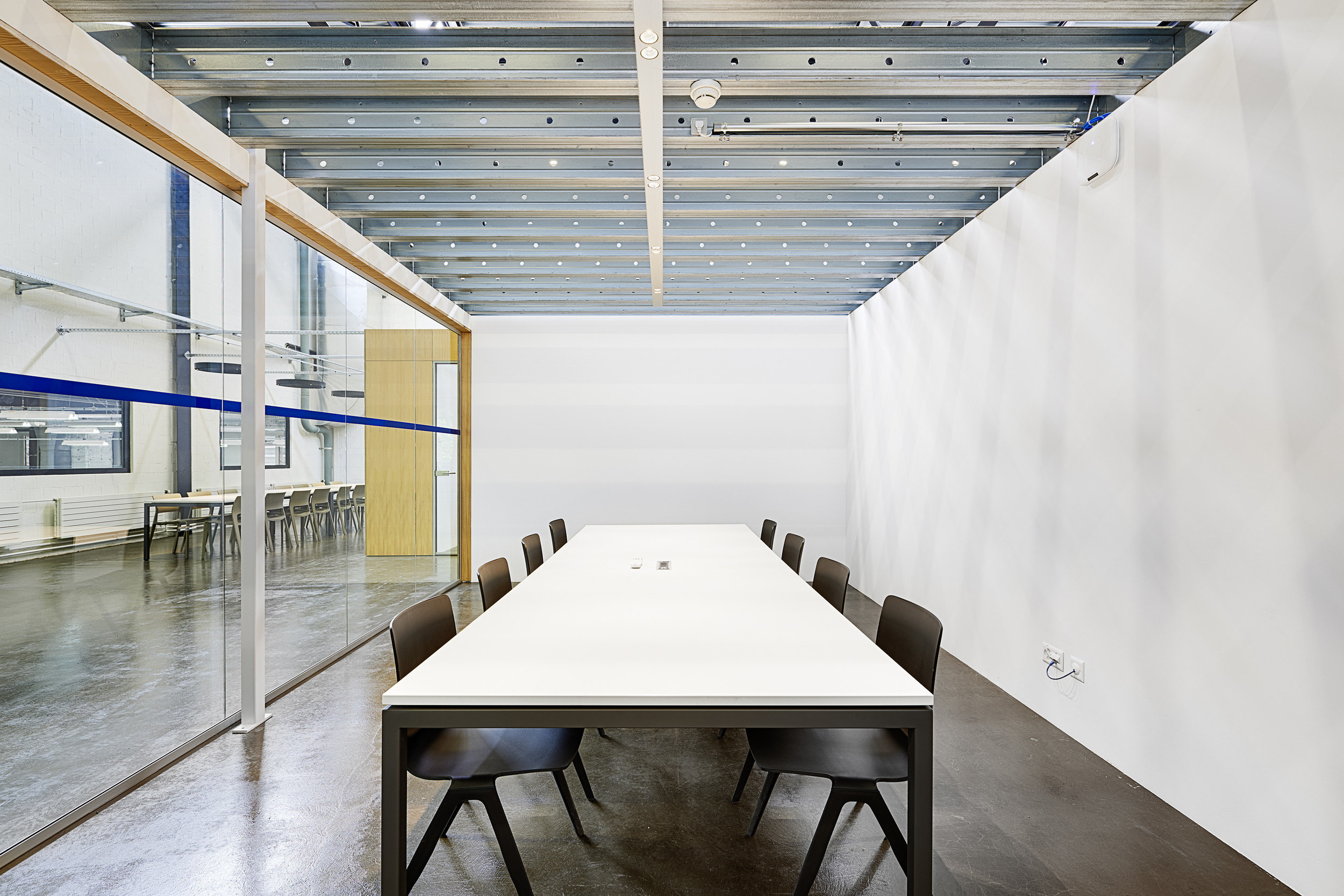 Indoor-Raum mit raumhoher Fensterwand und bestuhltem Tisch