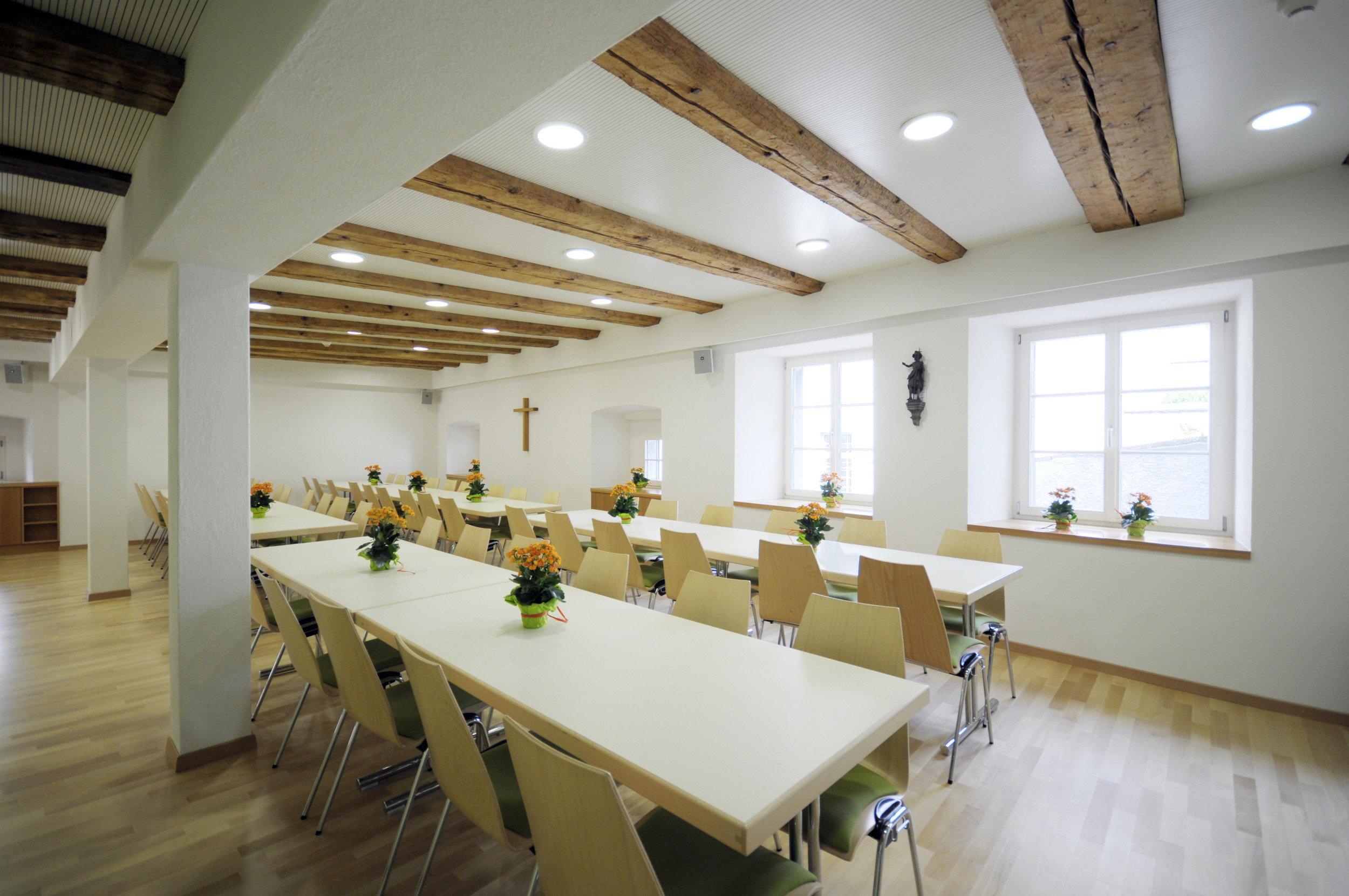 Renovierter Pfarrsaal gestuhlt mit alten Holzbalken in der Decke
