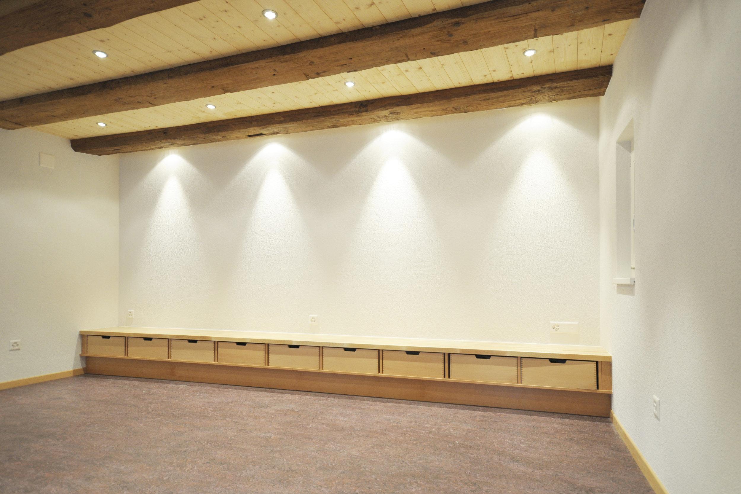 Raum mit Sitzmöglichkeit aus Holz und beleuchteter Wand