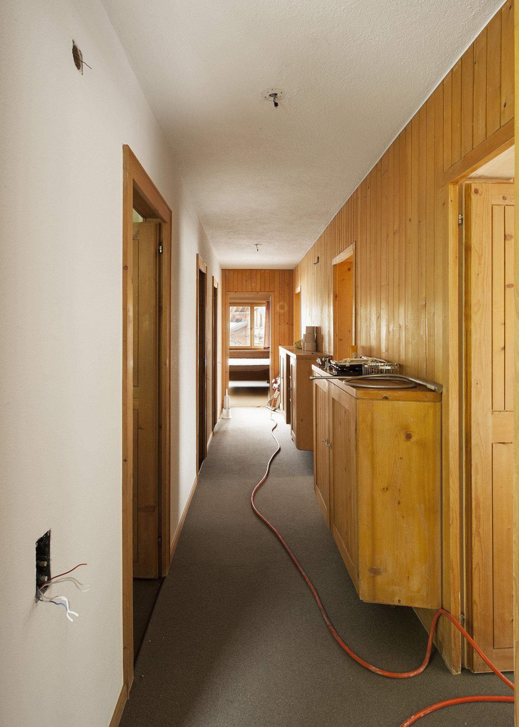 alter Flur mit Holzwänden, Teppichboden und Wandmöbel aus Holz