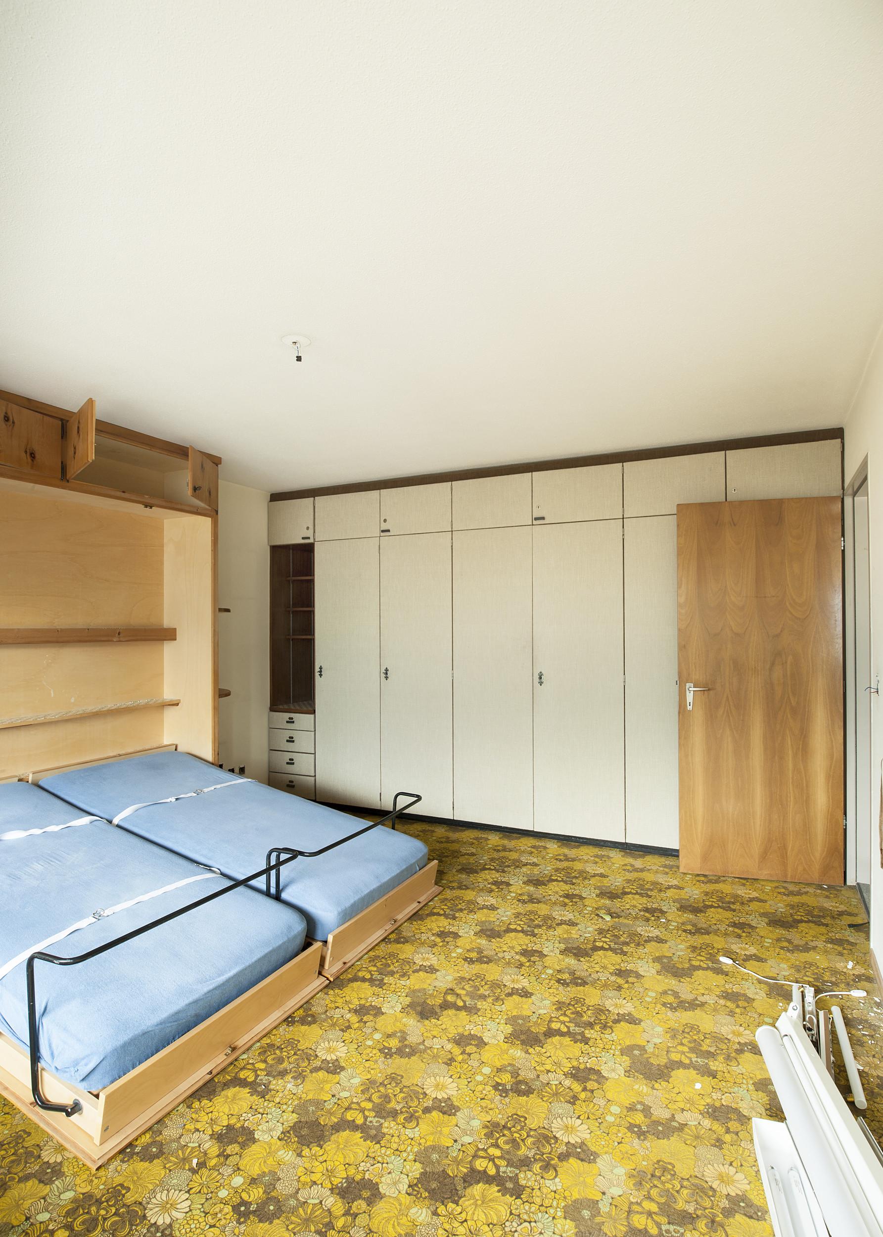altes Schlafzimmer mit weissen Schränken und Boden mit Blumenmuster