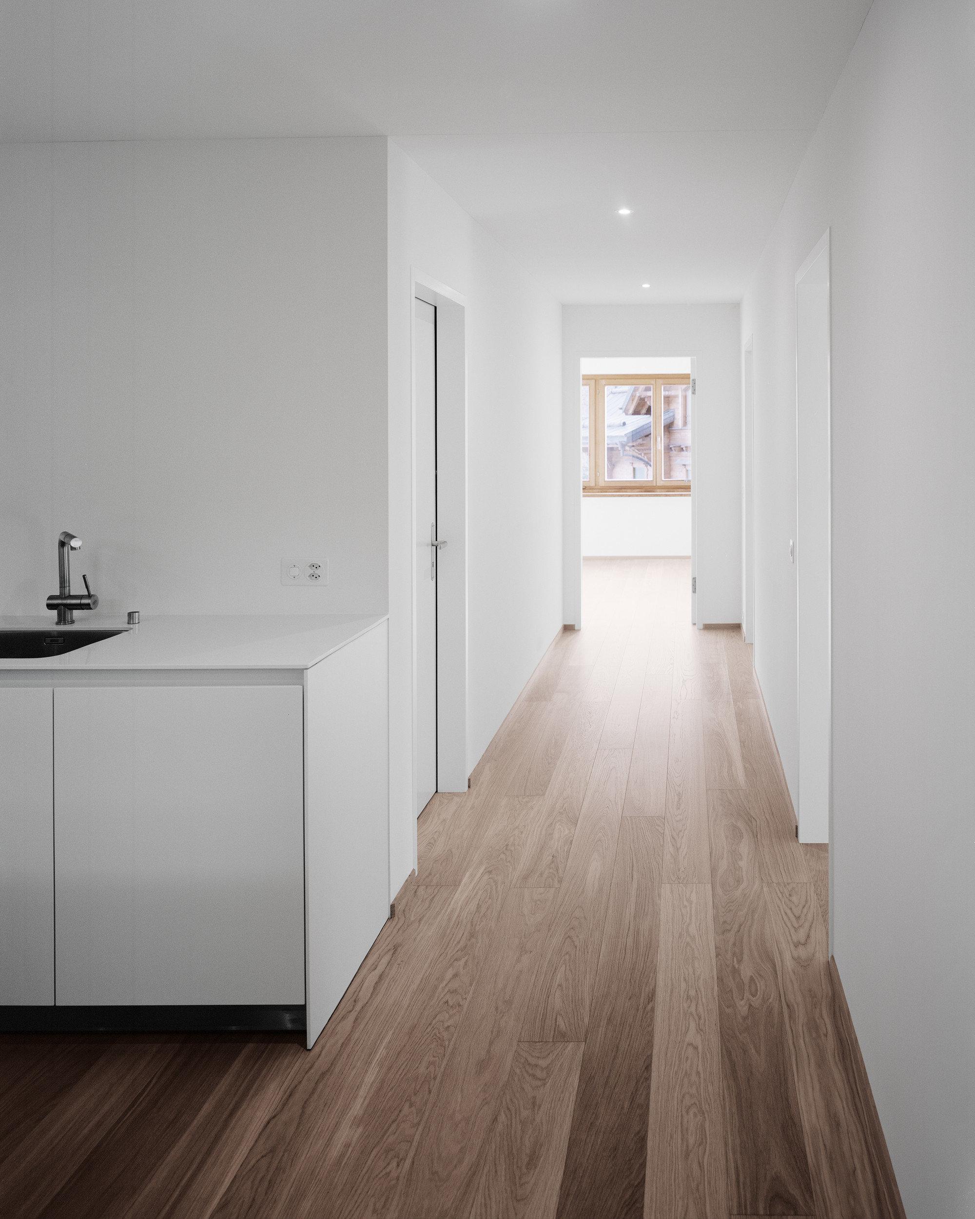 Küchentheke links, neuer dunkler Holzboden, sanierte weisse Wände