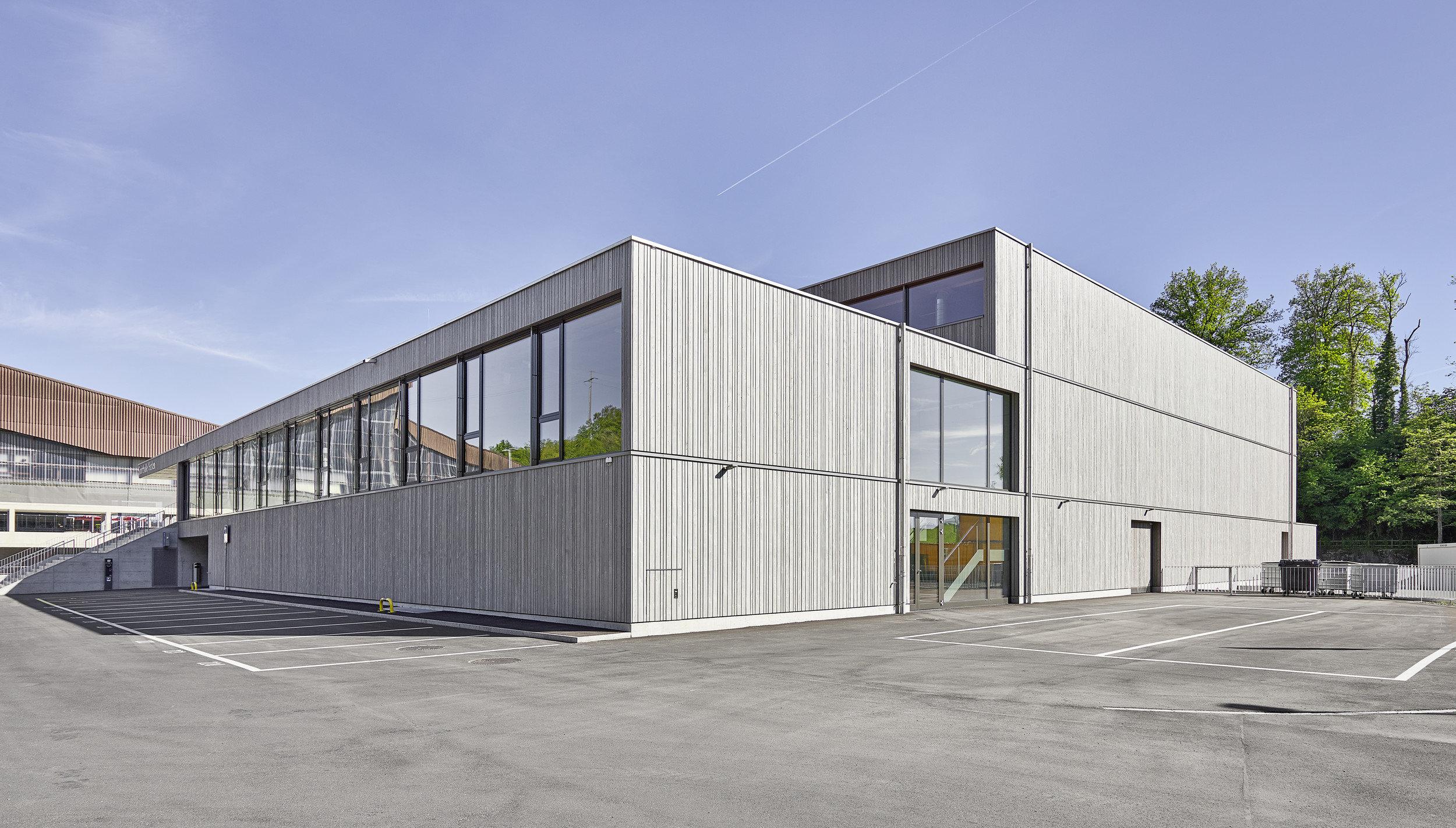 Gross-Sporthalle von aussen mit Fassade aus Fichtenholz allwettergrau