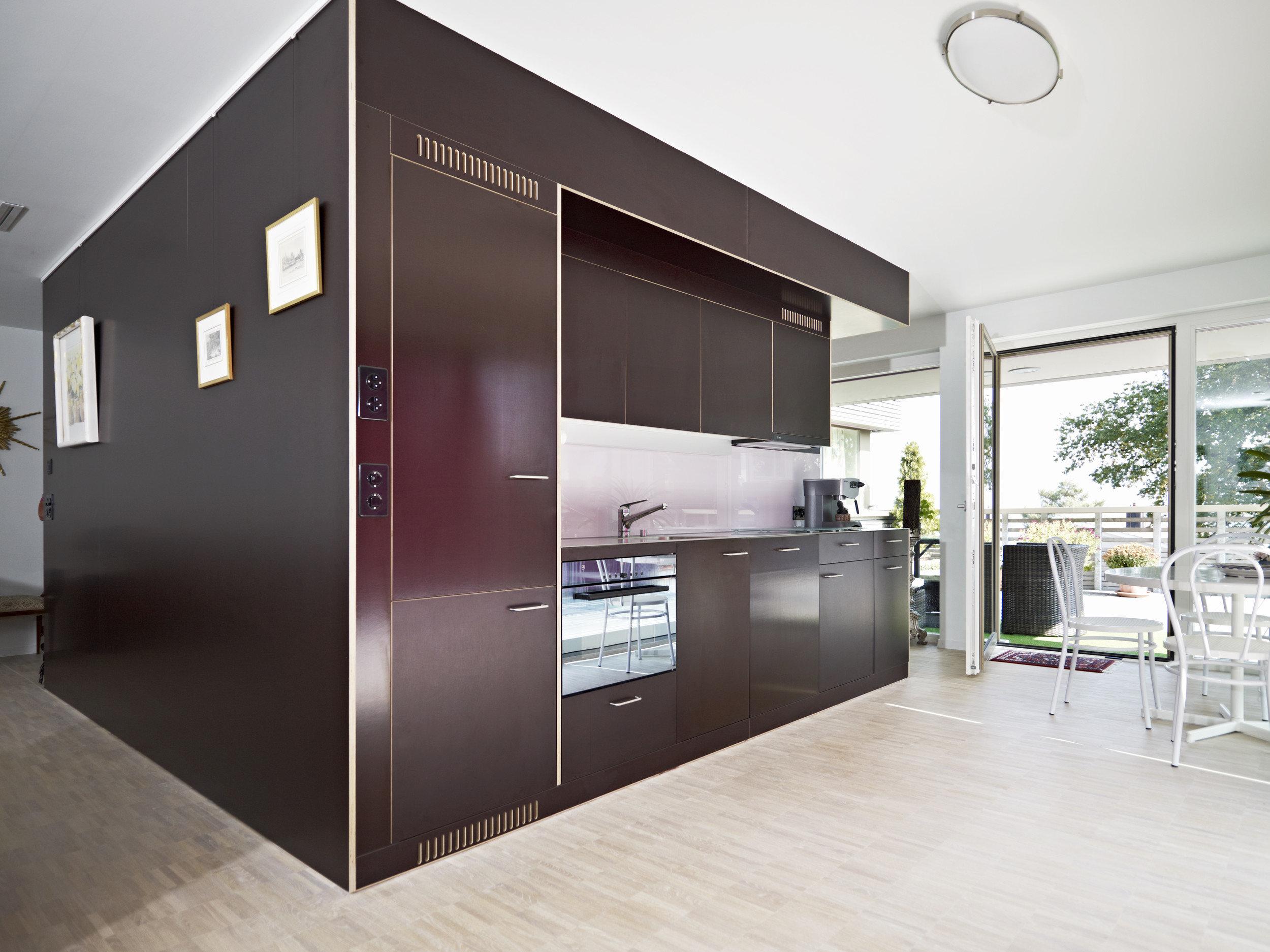 Einbauküche aus dunklem Holz im Raum mit viel Sonnenlicht und hellem Holzboden