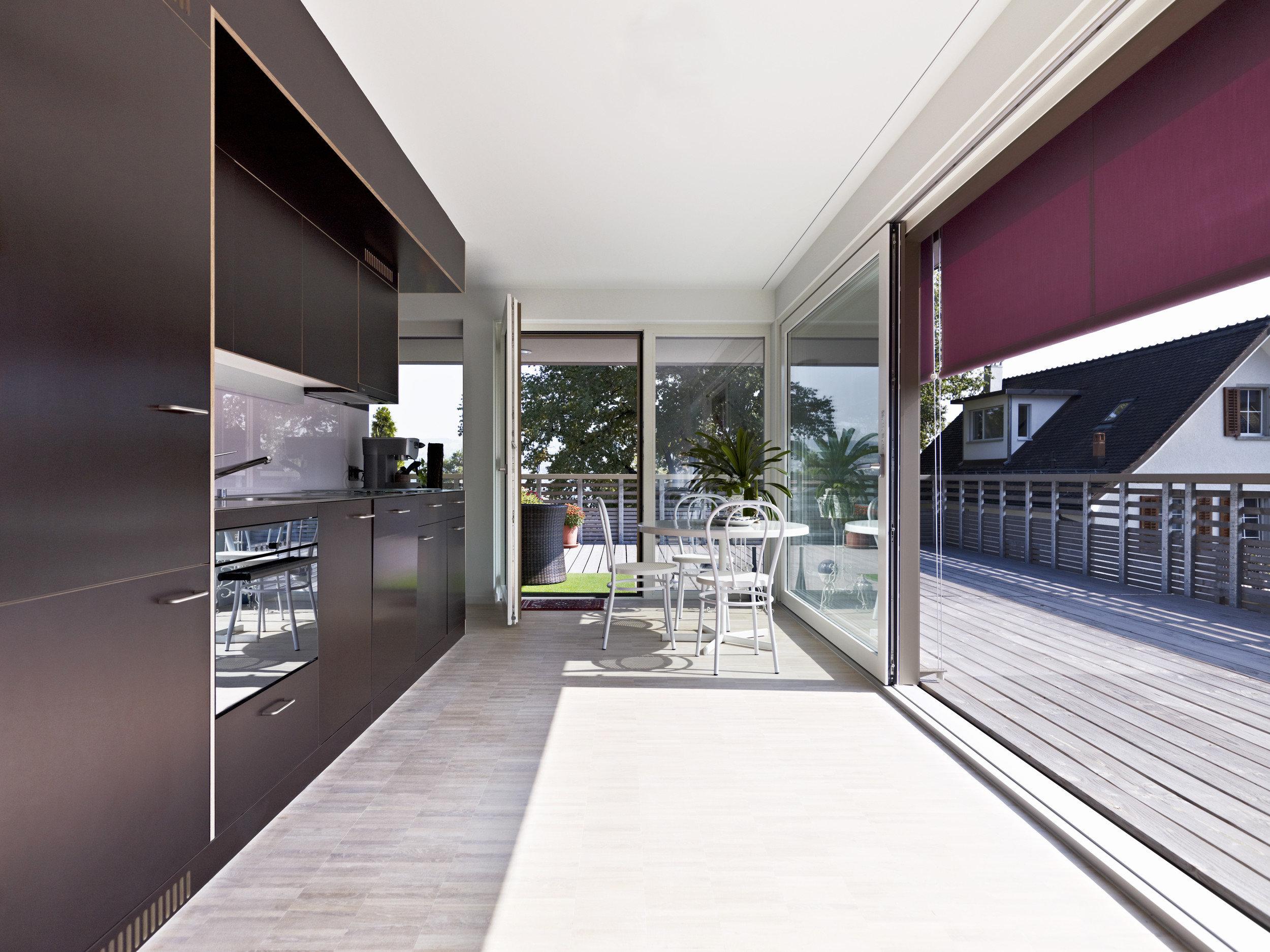 Einbauküche aus Holz und grosser Hebe-Schiebetür mit Esszimmerfläche