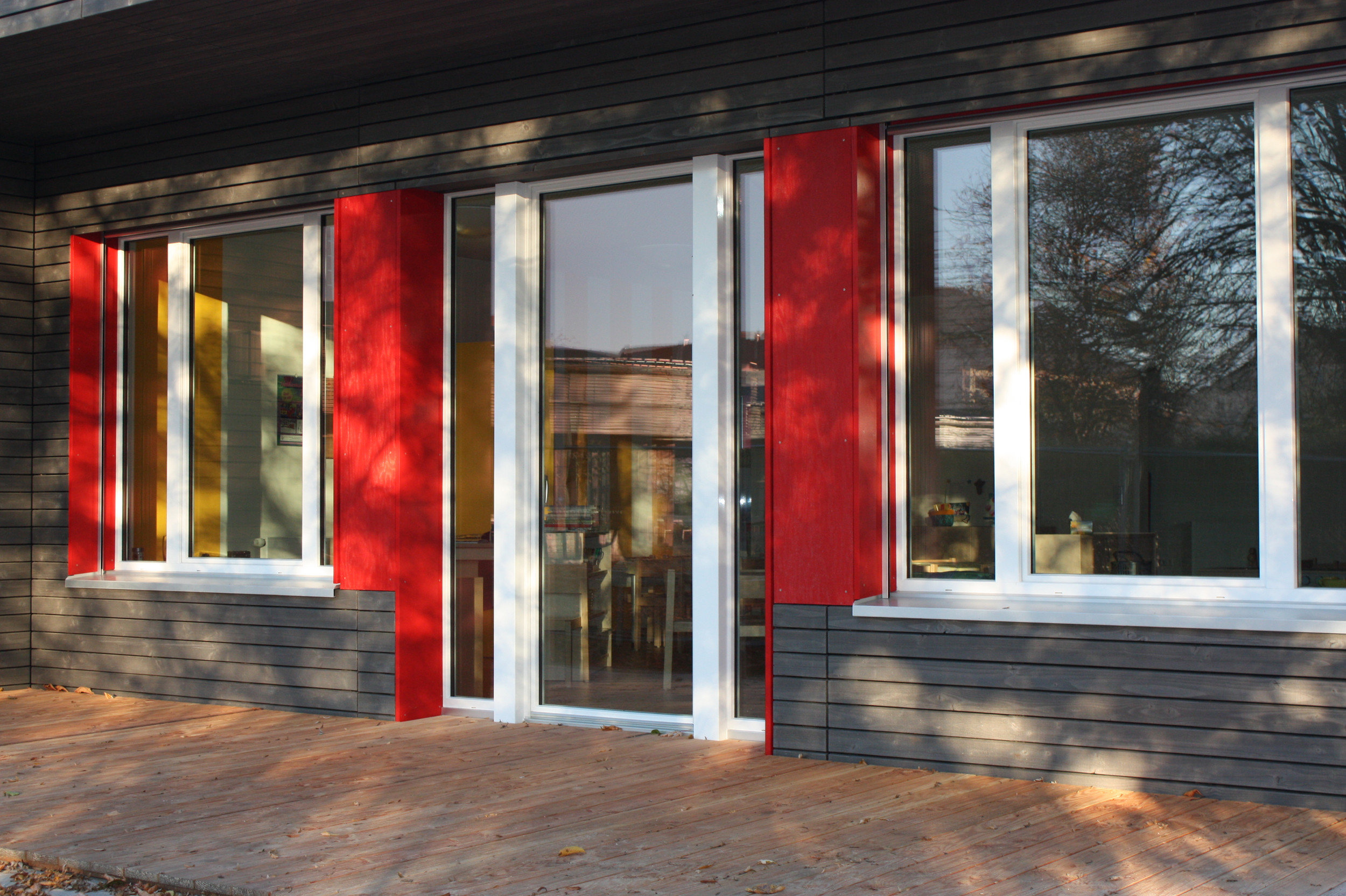 Eingang zwischen zwei gleich grossen 3-teiligen Fensterelementen