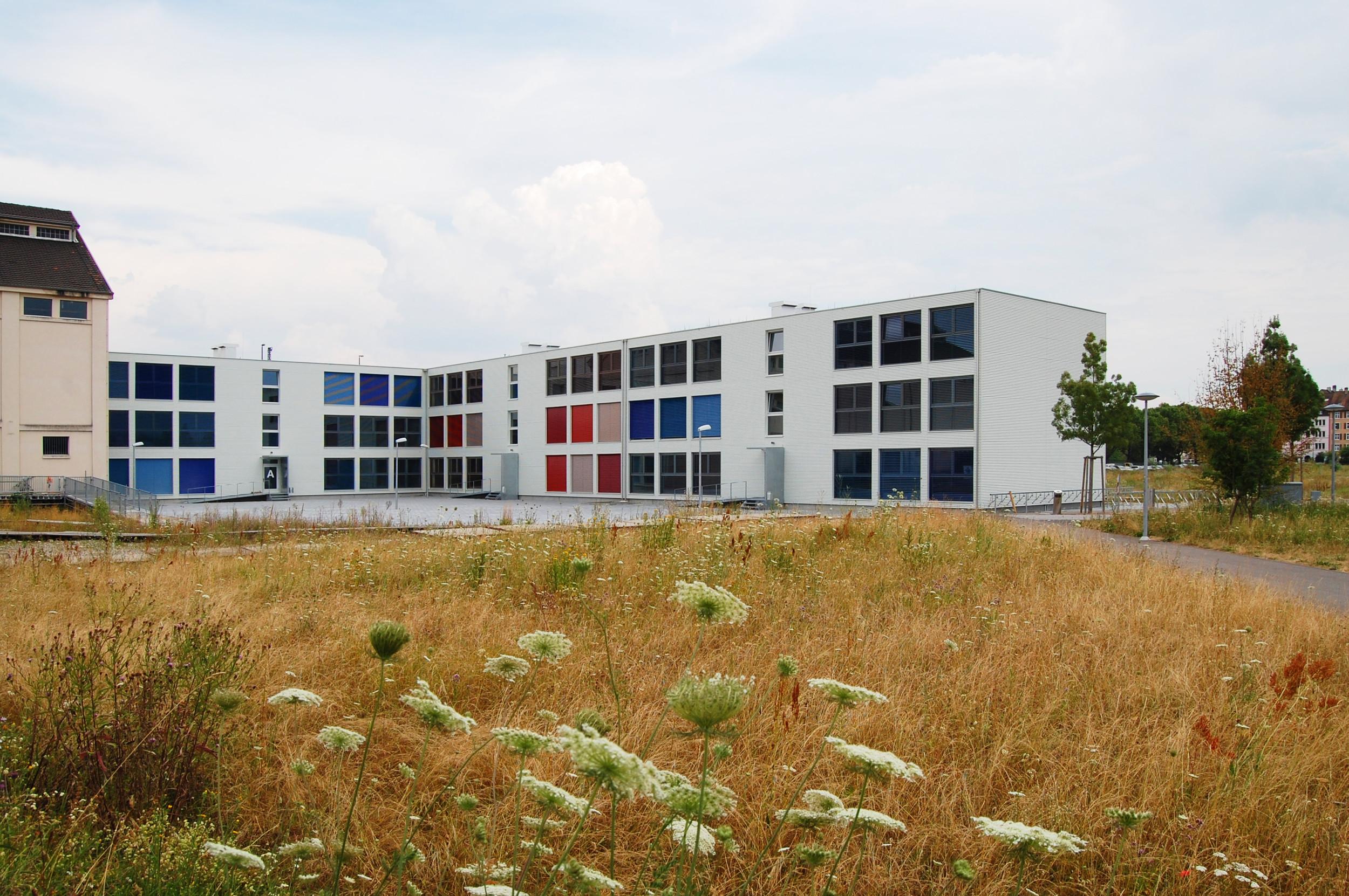 2-stöckiges Schulgebäude in L-Form in Modulbauweise mit gleichmässiger Fensteranordnung