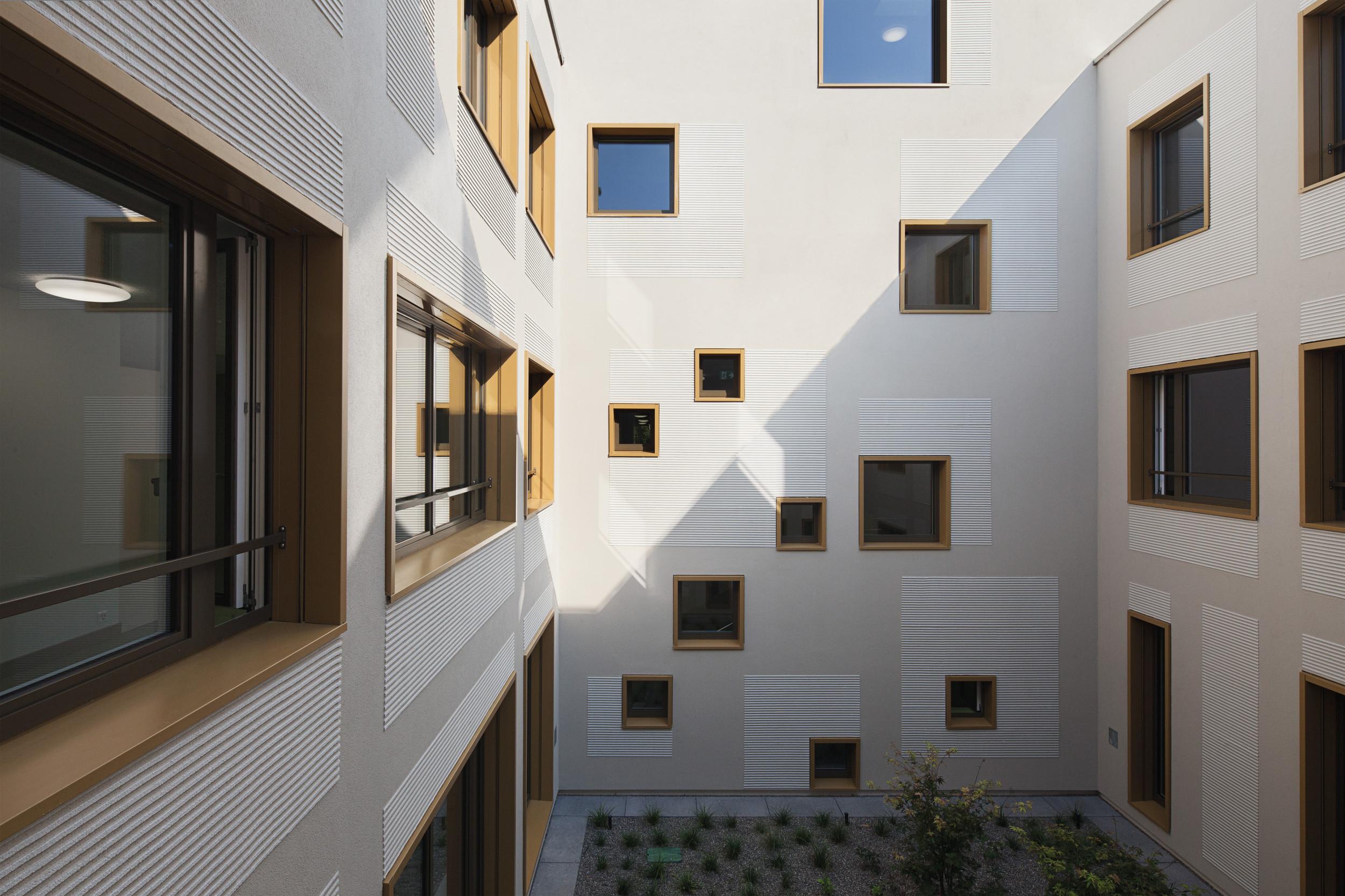Mehrstöckiges Gebäude mit Holz-Elementfassade und verschiedenen Fenster