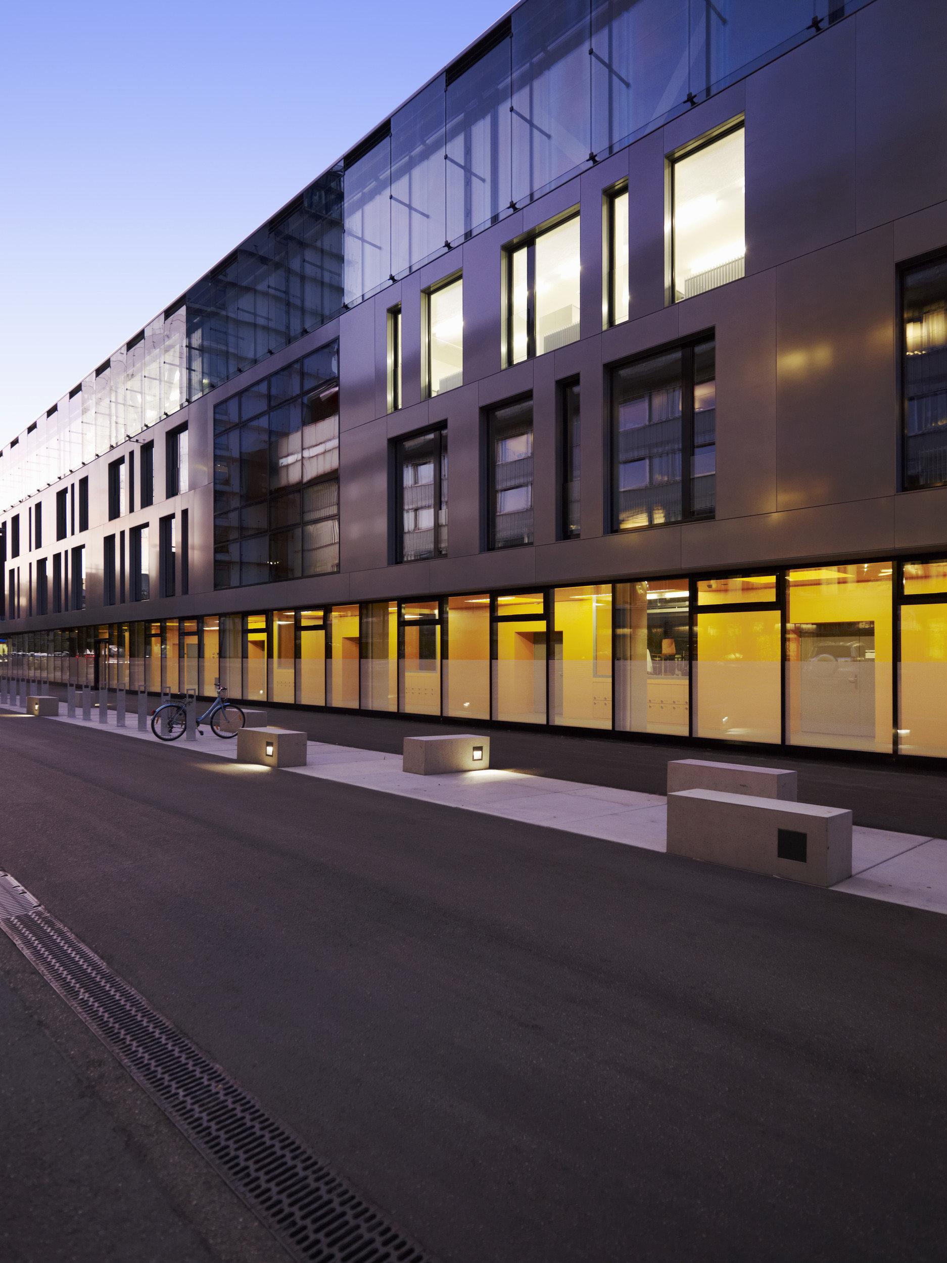 Langes Gebäude mit grosser Holzfassade und grossen Holz-Metallfenster