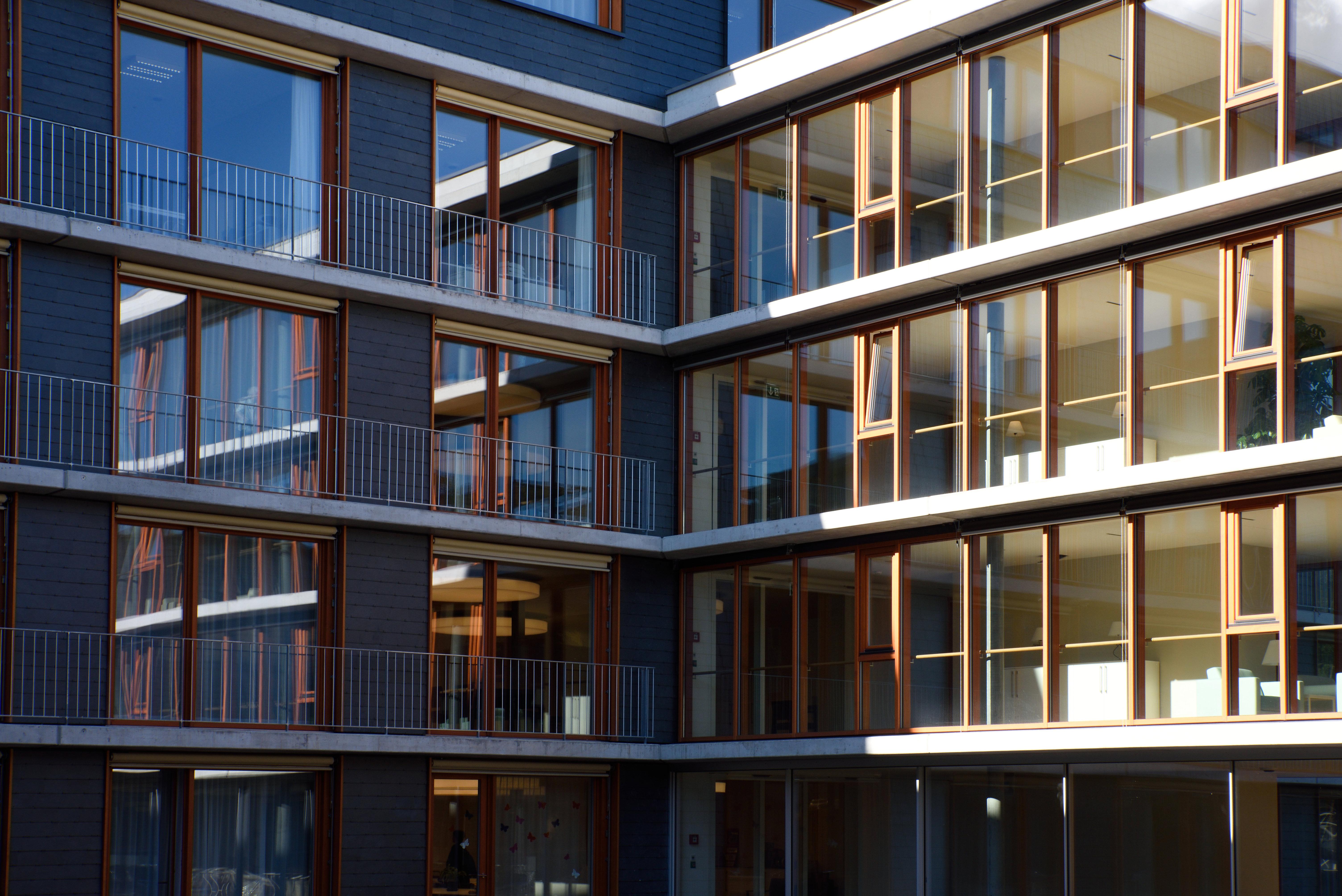 Mehrgeschossiges Wohngebäude mit raumhohen Fenstern und Pfosten-Riegelelemente in Naturholz