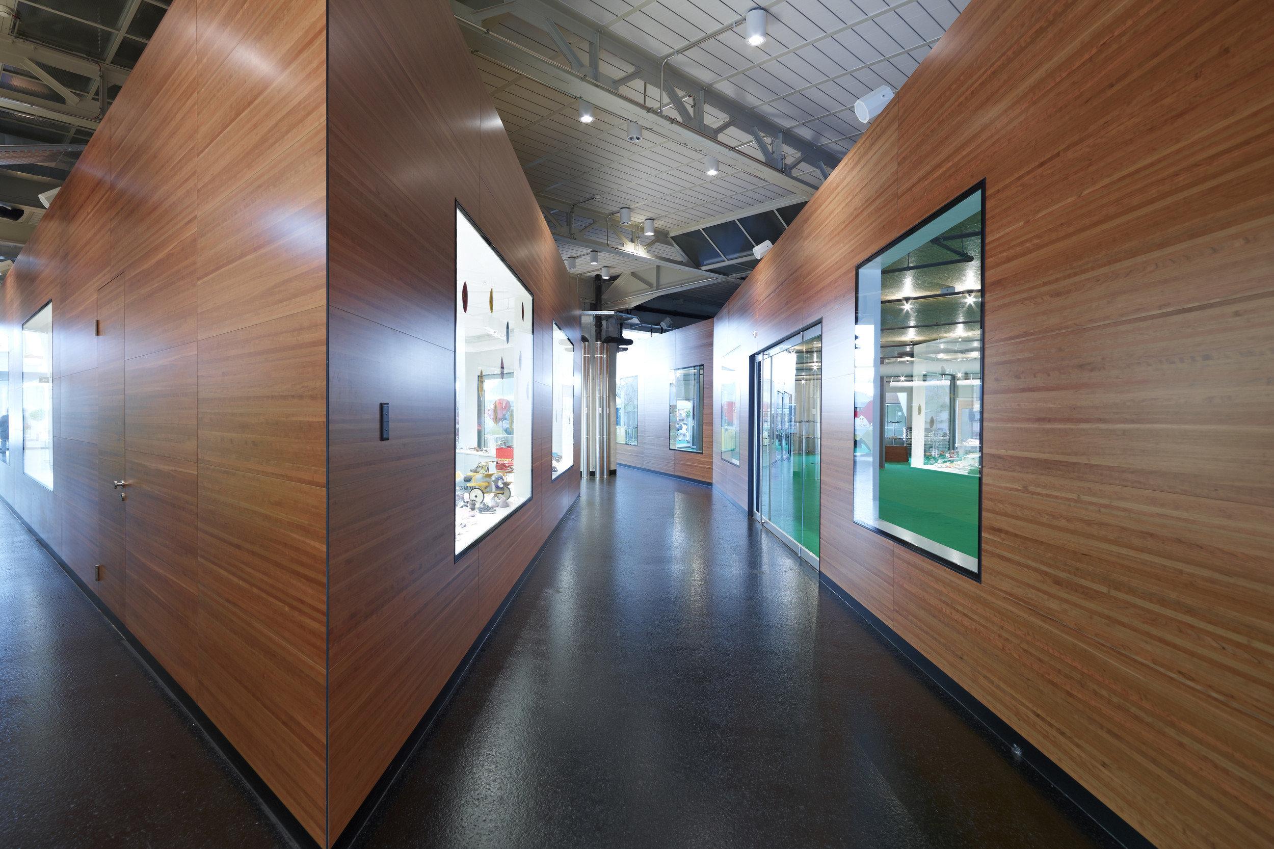 2 Shop-in-Shops aus Holz in Betonhalle mit grossen beleuchteten Fenstern