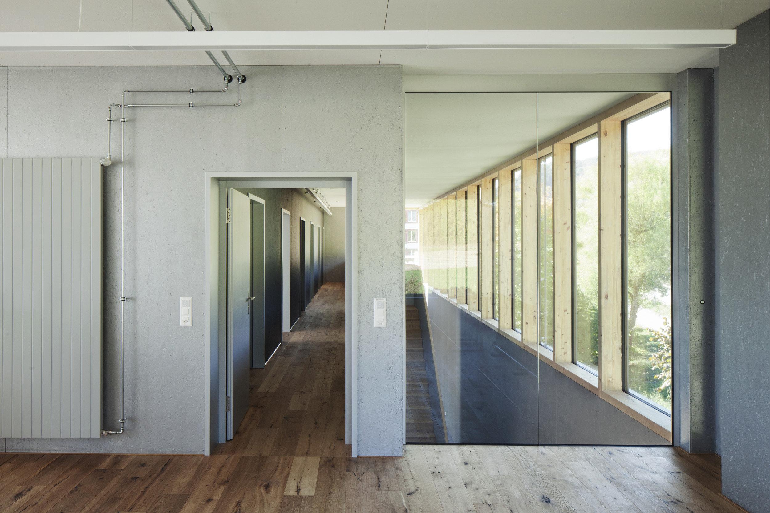 Raumhohe Fenster-Front in Flur mit Glas- und Betonwänden