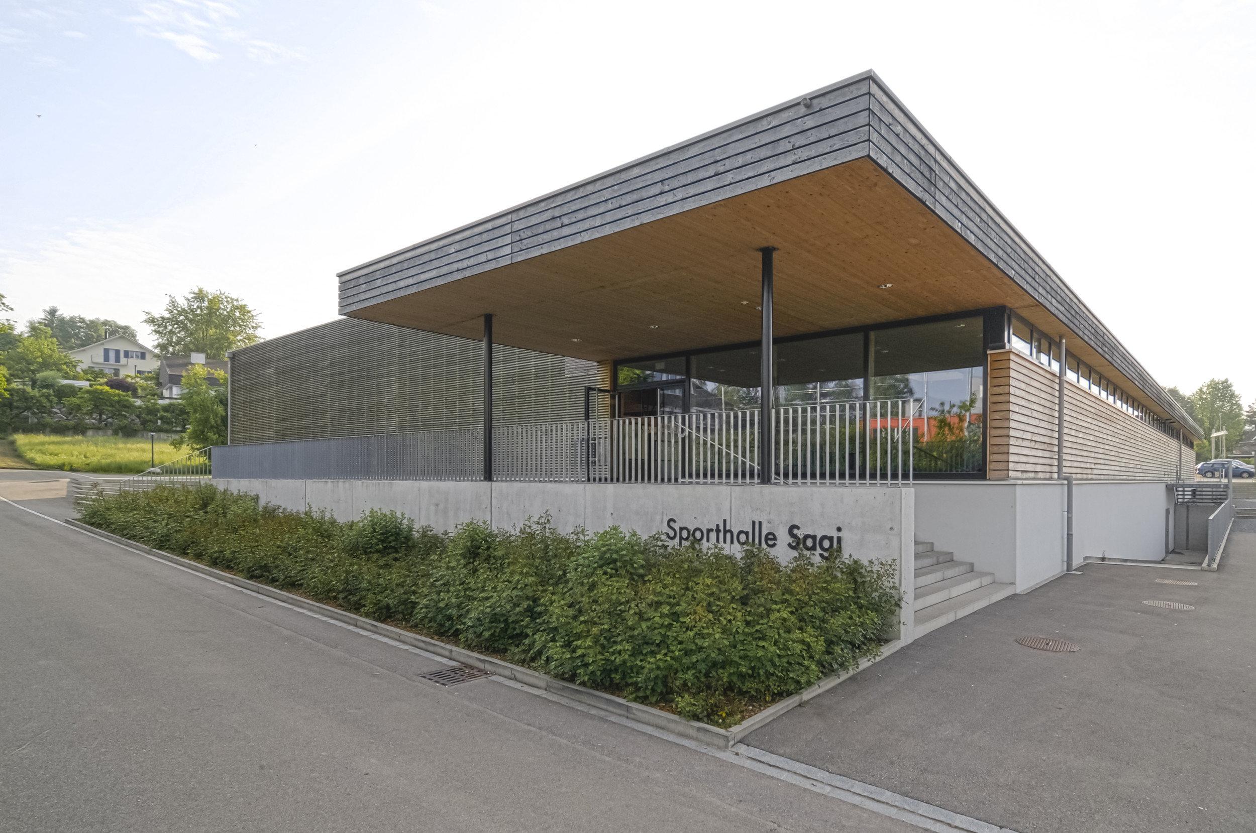 überdachter Eingang von Sporthalle mit Holzfassade