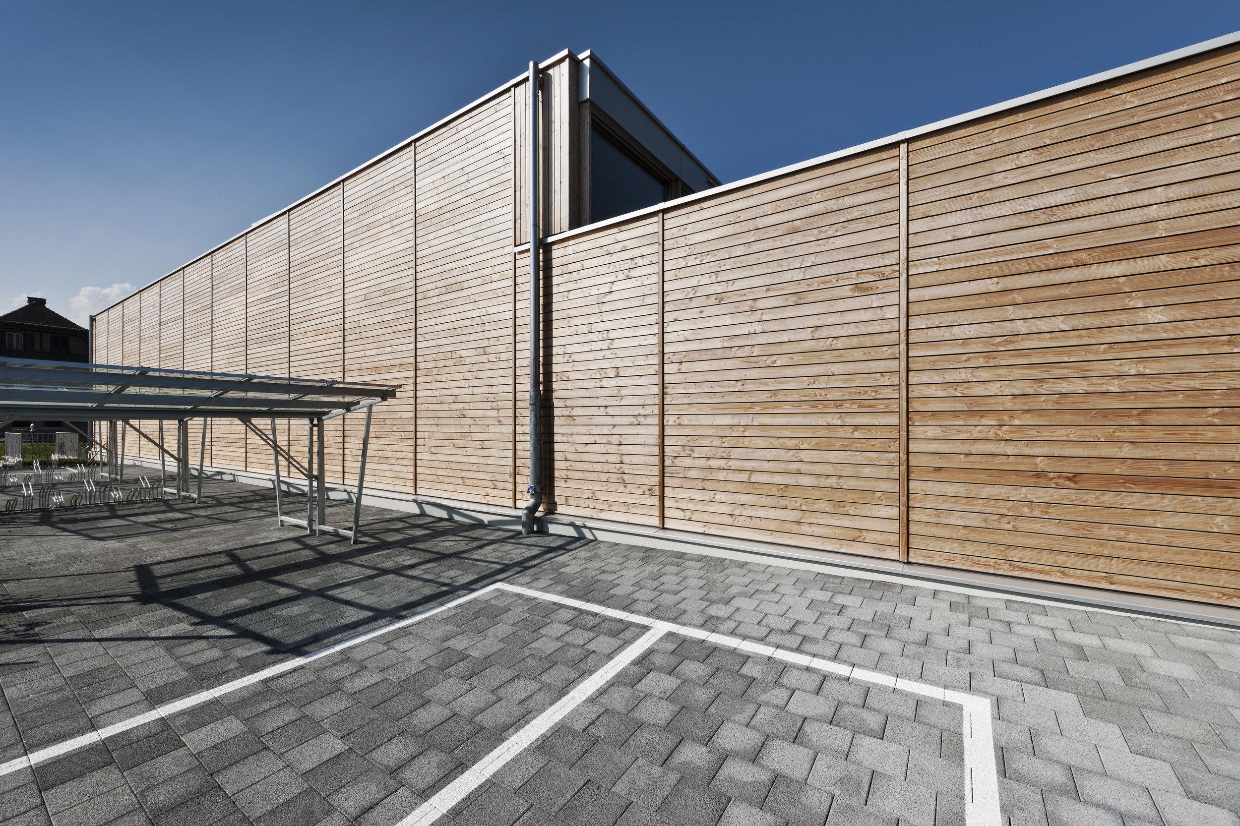 Turnhalle mit Holzfassade ohne Fenster