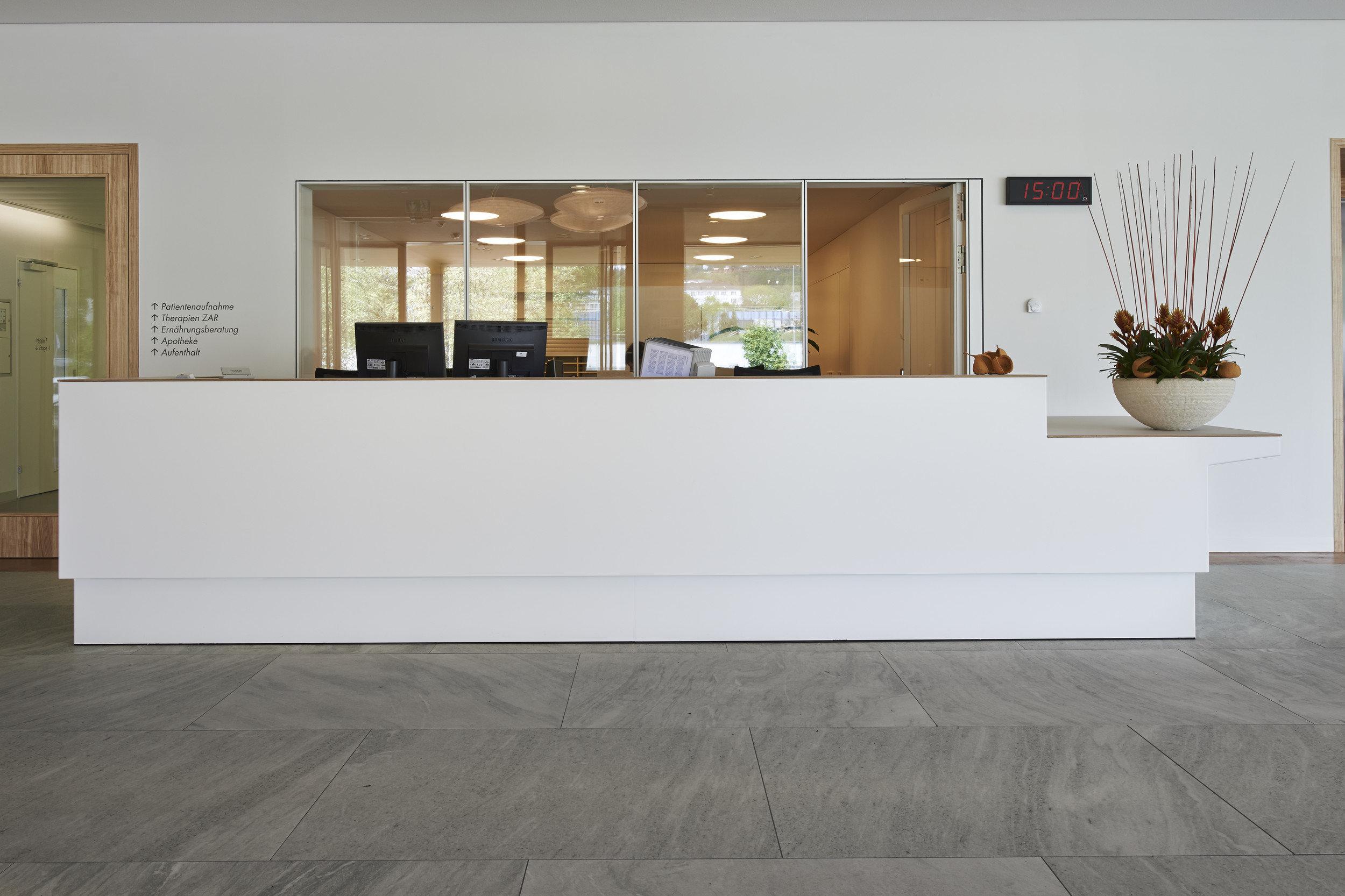 Weisse Empfangstheke aus Holz mit grosszügiger dahinter liegender Glasfläche