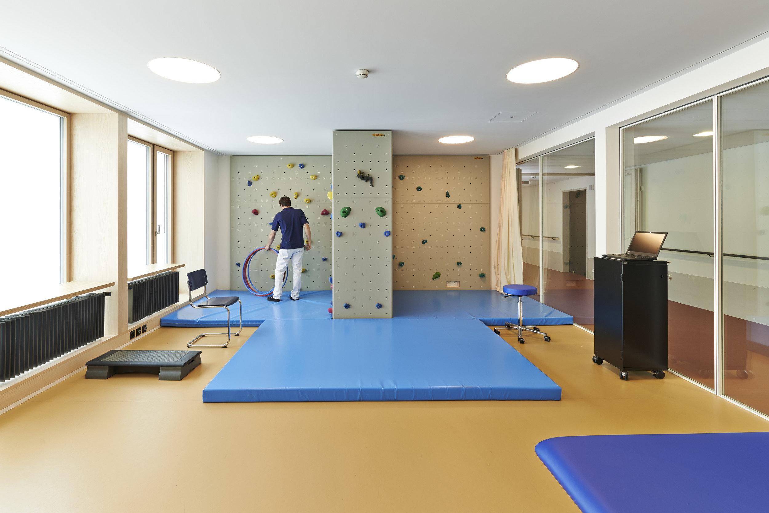Raum mit Rehabilitationsmöglichkeiten mit Indoorfenstern als Wand zum Flur