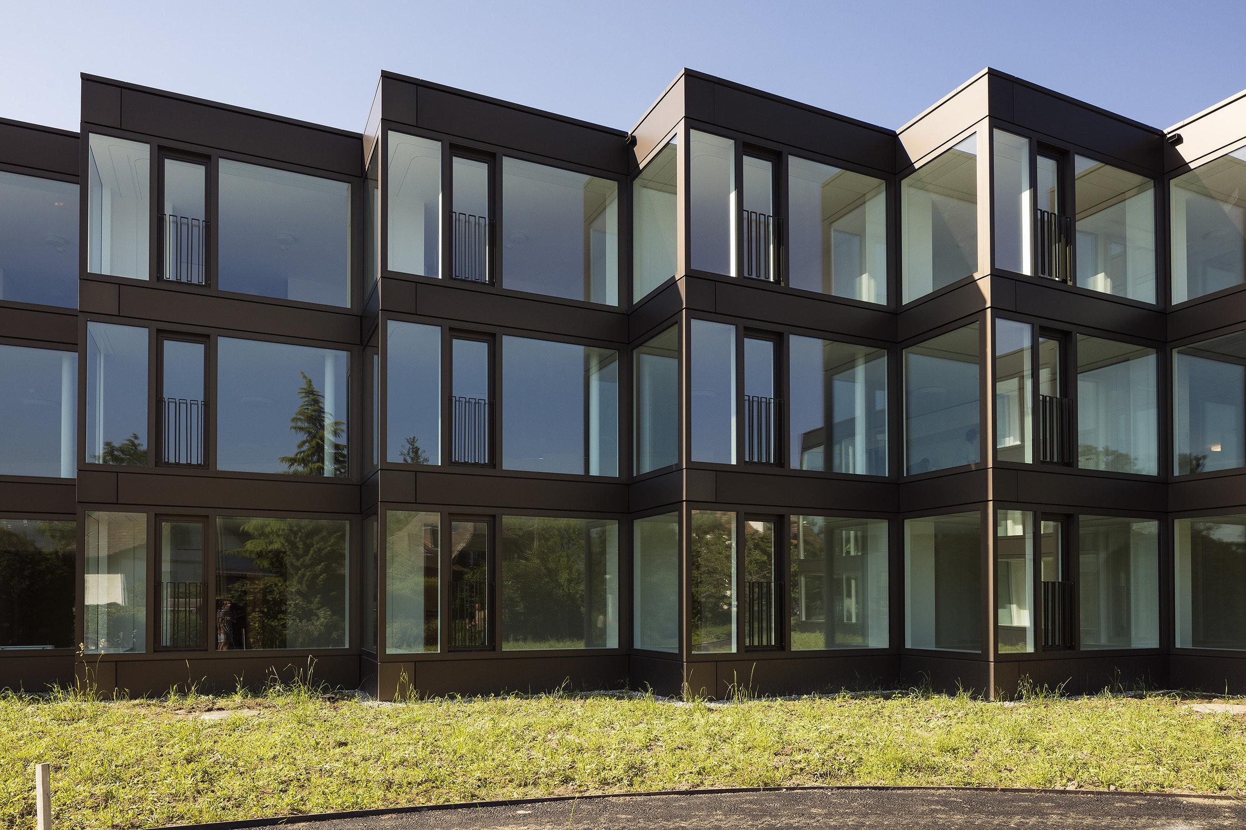 Fensterfront mit wenig Fassade bei Gebäude im zick-zack-Muster