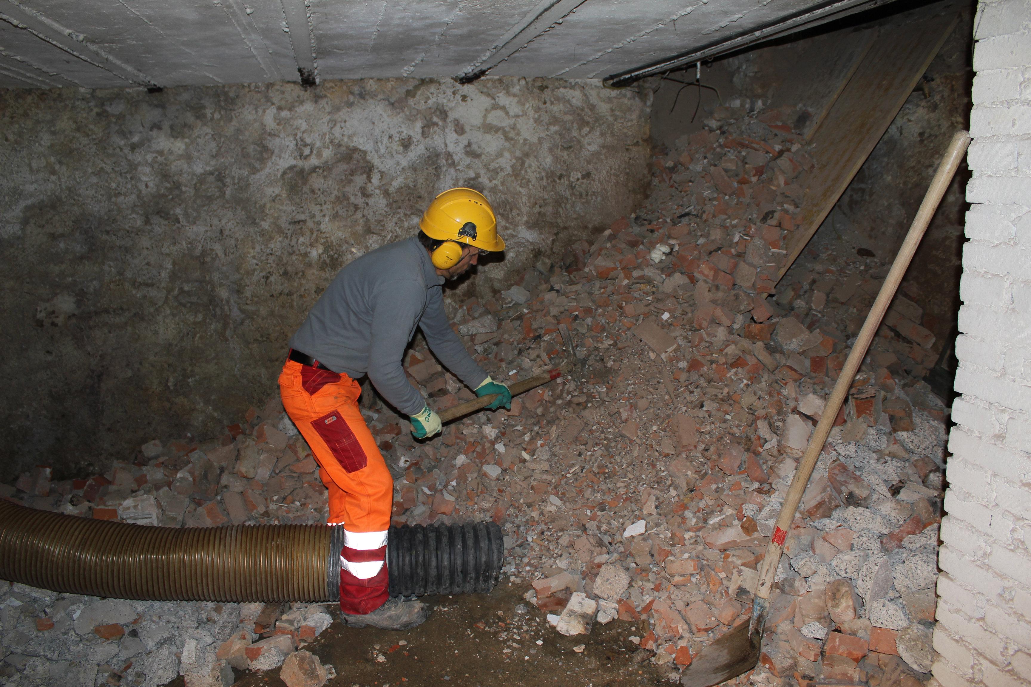Saugbagger, Arbeiter befördert Bauschutt zum Saugrohr